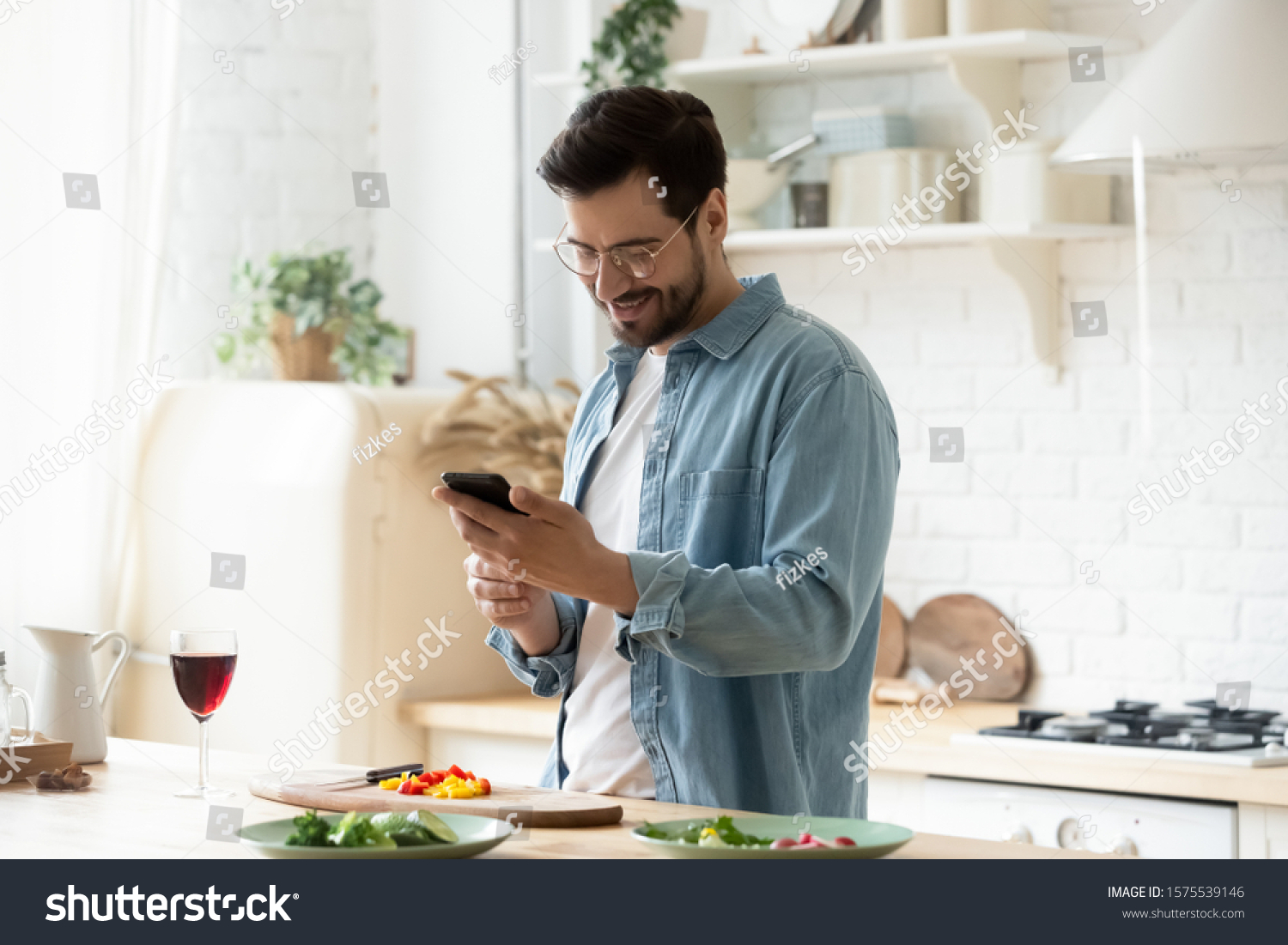 Happy young man preparing romantic dinner searching vegetable recipes diet menu cookbook app using smartphone, smiling husband holding phone cooking healthy vegan food cut salad in kitchen interior #1575539146