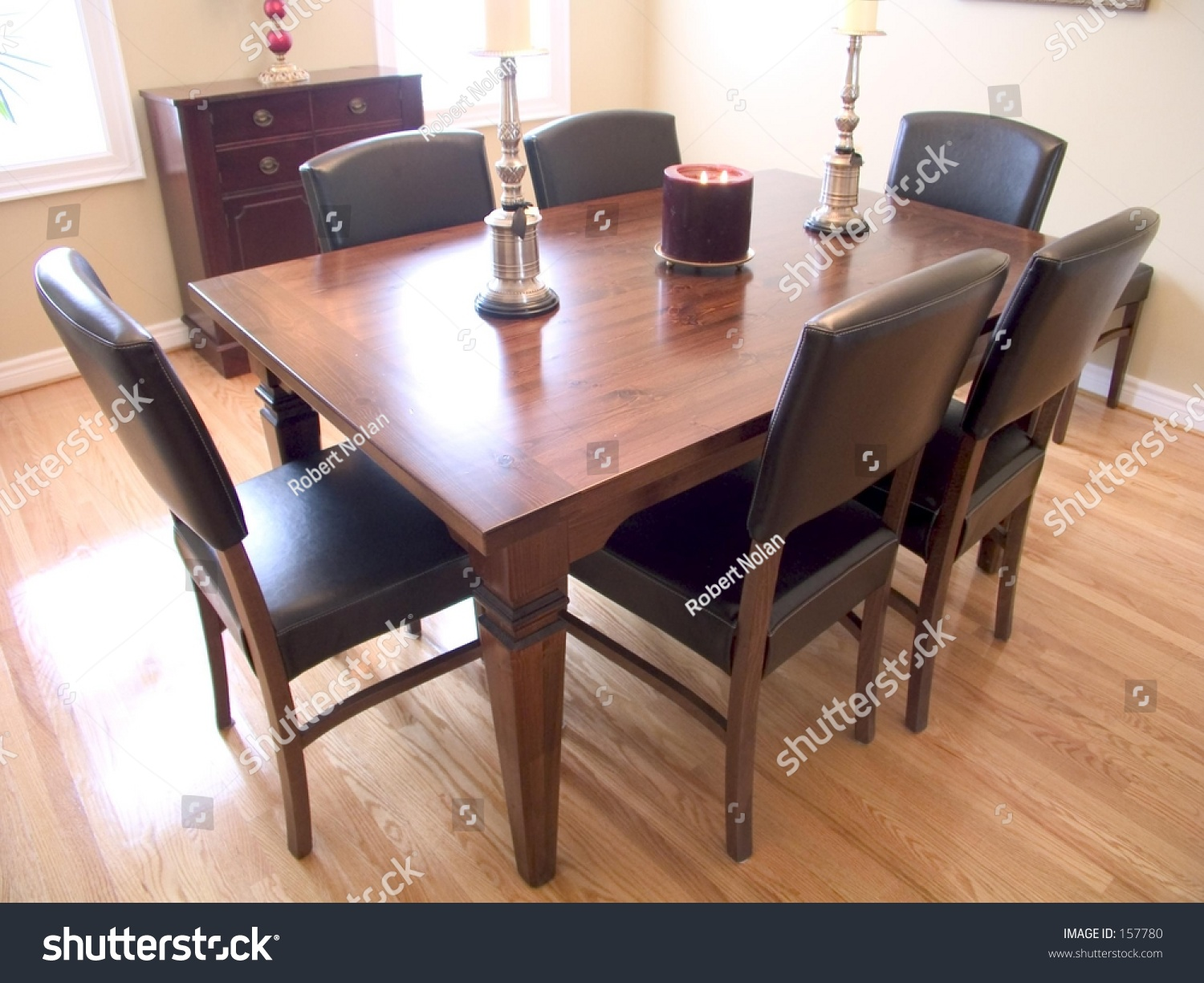 stock photo dining room with dark wood table six chairs candelabra and two windows with a natural wood floor