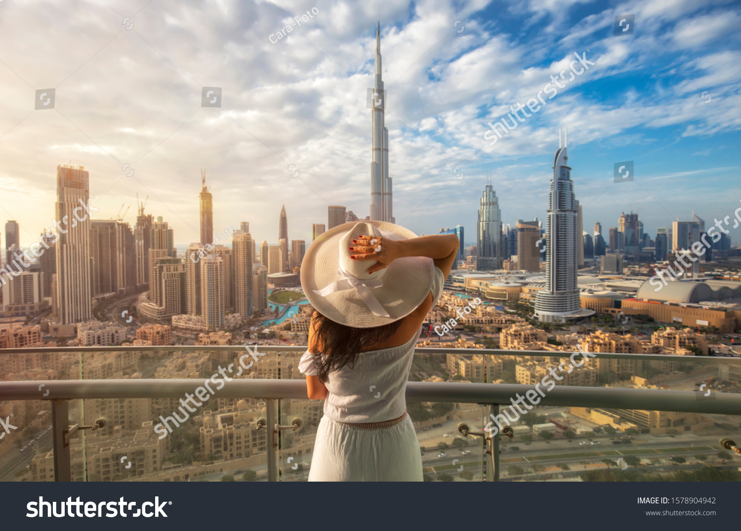 Woman with a white hat is standing on a balcony in front of the skyline from Dubai Downtown #1578904942