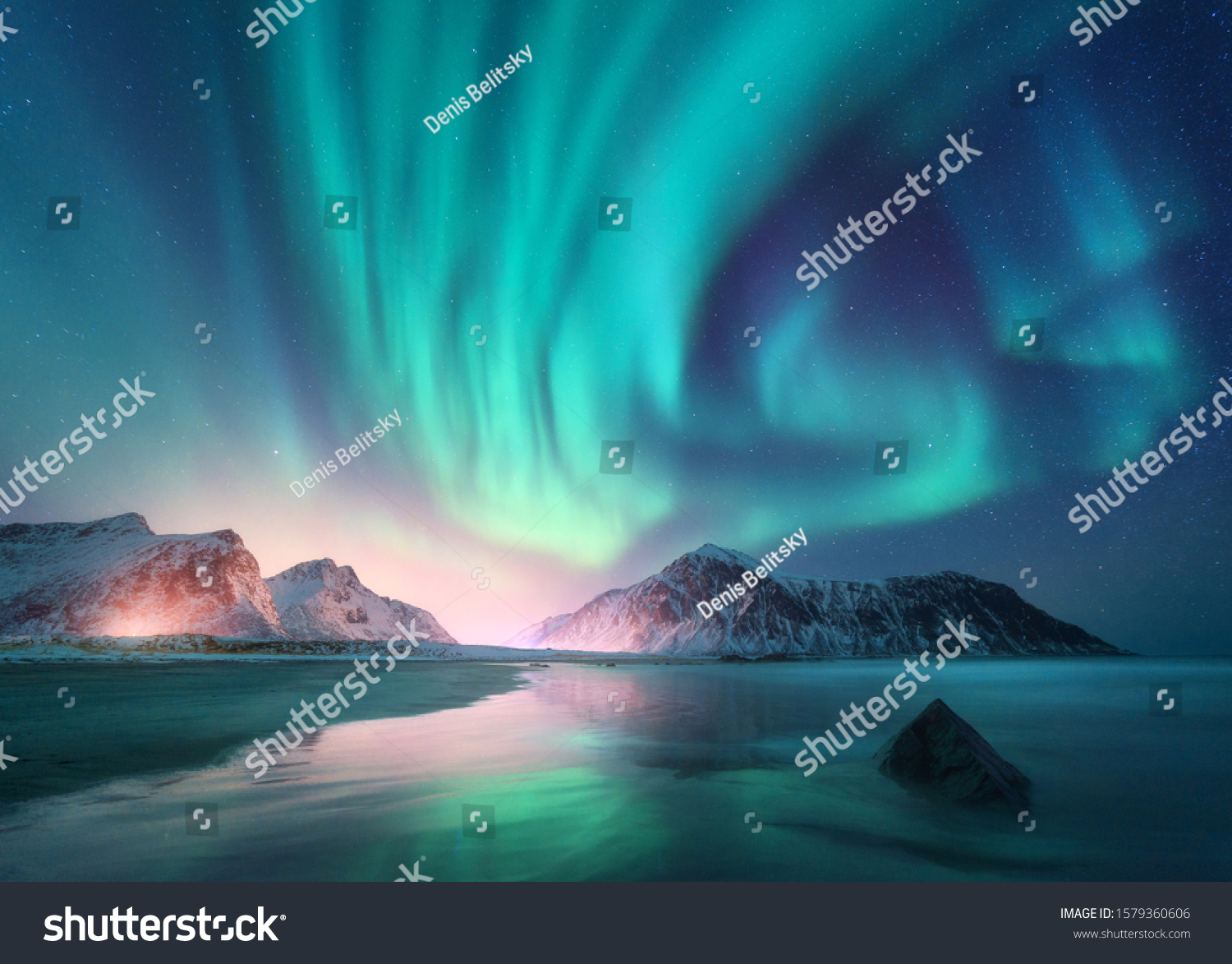 Aurora borealis over the sea, snowy mountains and city lights at night. Northern lights in Lofoten islands, Norway. Starry sky with polar lights. Winter landscape with aurora, reflection, sandy beach  #1579360606