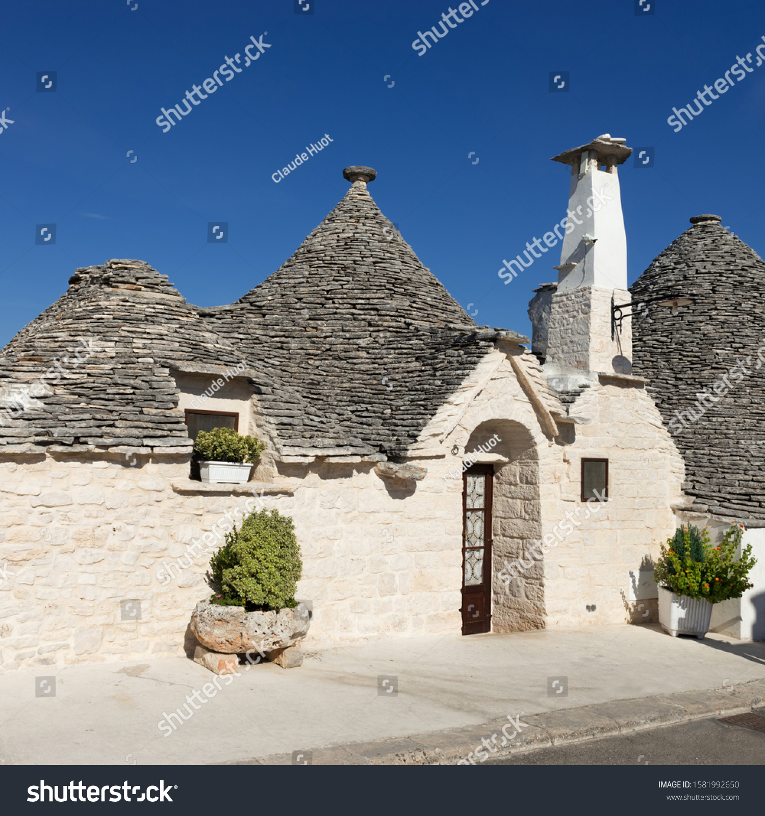 Street view of famous trulli in the town of Alberobello, a small town of the Metropolitan City of Bari, Apulia, Italy. The trulli have been designated as a UNESCO World Heritage site since 1996.