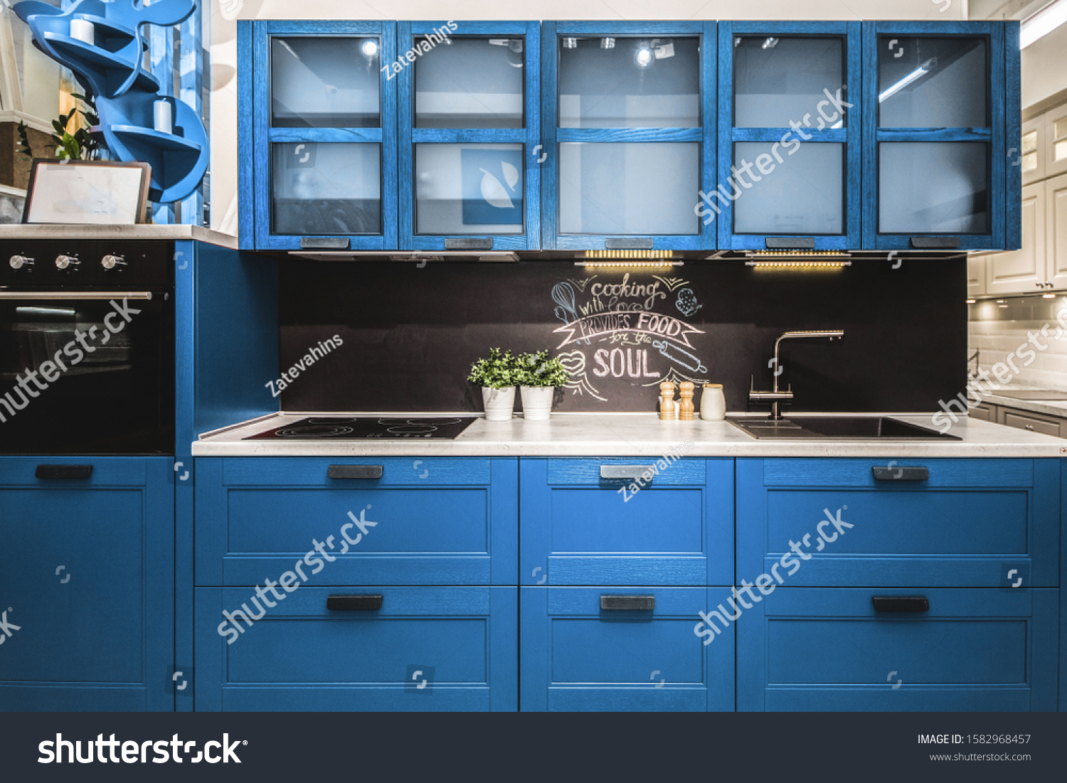 Modern red kitchen interior with black brick walls, wooden countertops with a built in sink and a cooker.  color of the year 2020 pantone classic blue #1582968457