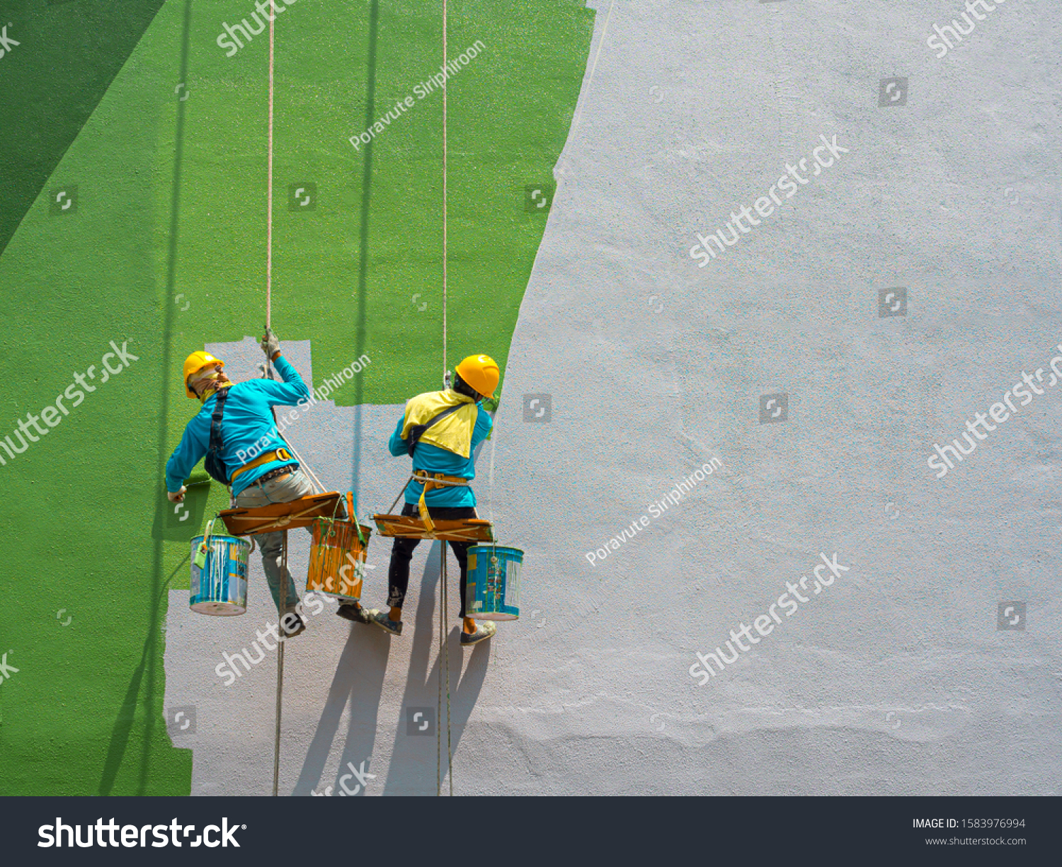 Two painters are painting the exterior of the building on a dangerous looking scaffolding hanging from a tall building with copy space. #1583976994