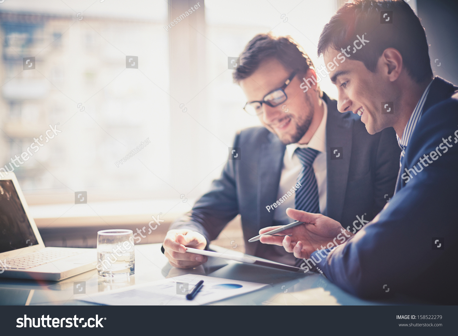 Image of two young businessmen using touchpad at meeting #158522279 - 123PhotoFree.com