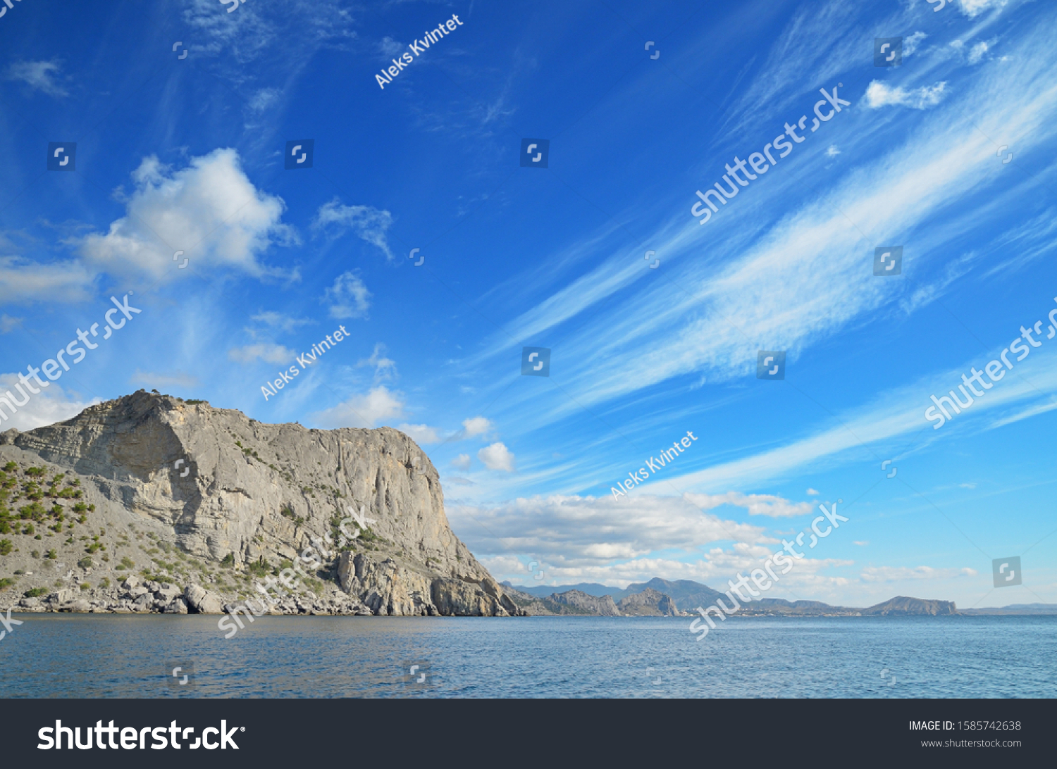 View of the steep rocky slope of Mount Eagle (Koba-Kaya) against a bright blue sky and white clouds. Coast of the Black Sea, eastern Crimea, New World.