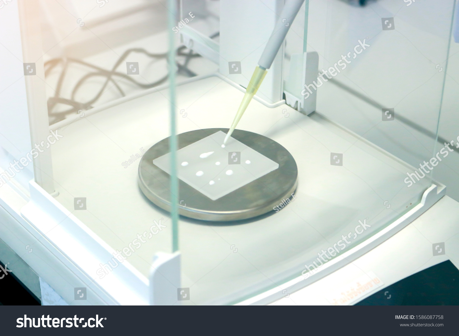 Scientist pipette a sample to sheet PMMA acrylic plate on analytical balance to know the exact weight before measuring the radiation protection of UV sunscreen cosmetic by using ultraviolet meter #1586087758