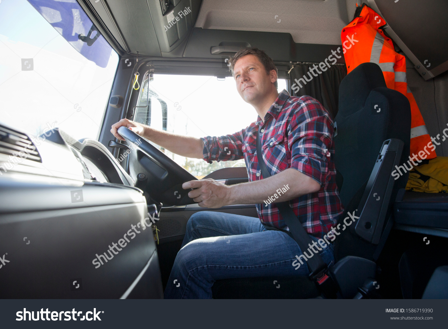 Truck driver driving in cab of semi-truck #1586719390