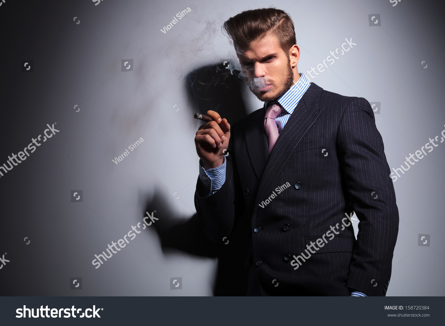 Serious Business Man Smoking His Cigar Stock Photo