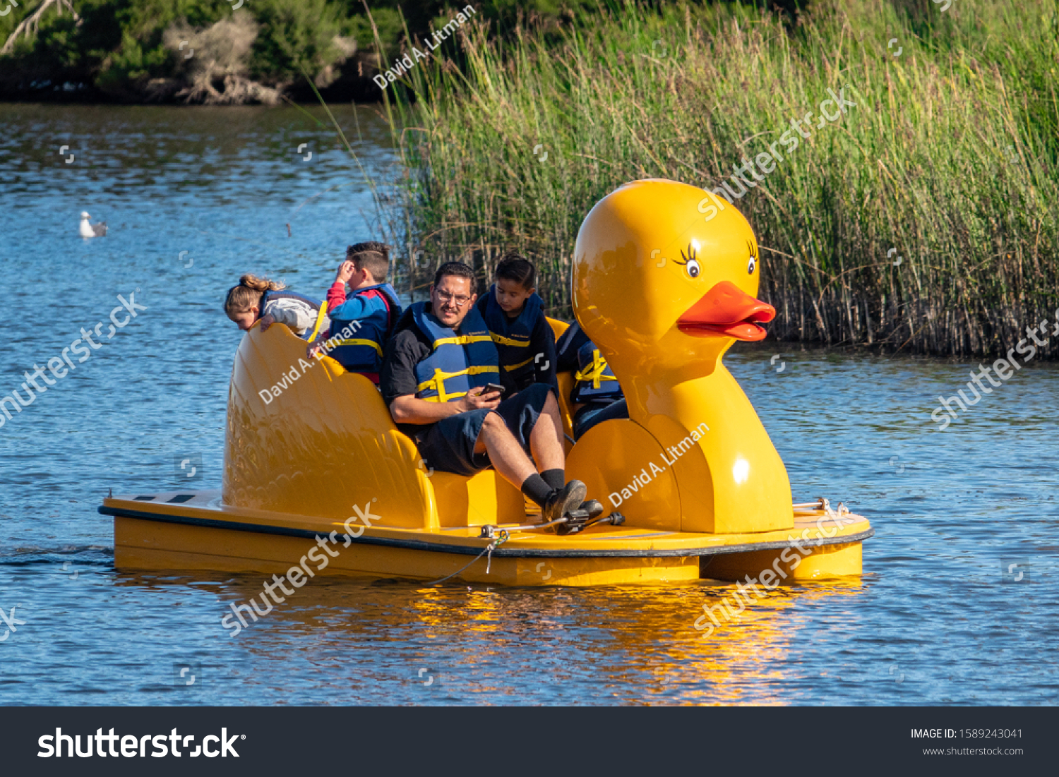 Monterey, California - December 14, 2019: A family enjoys the day on a yellow duck paddleboat on El Estero Lake, in Monterey, along the central coast of California.