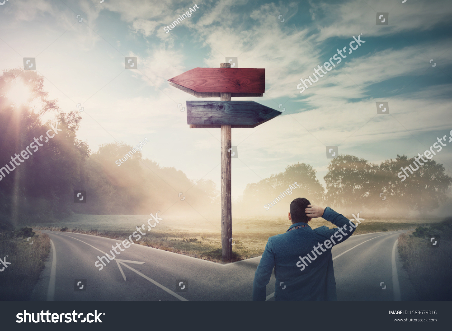 Rear businessman in front of crossroad and signpost arrows shows two different courses, left and right direction to choose. Road splits in distinct direction ways. Difficult decision, choice concept. #1589679016