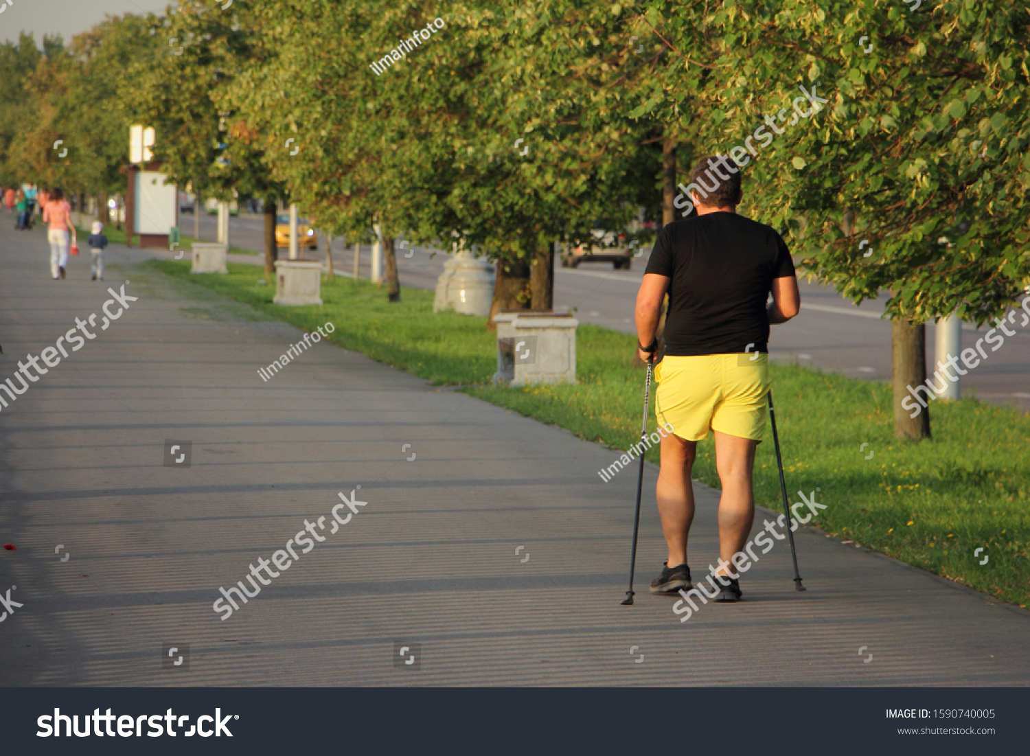 Nordic walking, man in black t-shirt and yellow shorts with ski poles walks through the Park alley on a summer day, back view against a trees background #1590740005