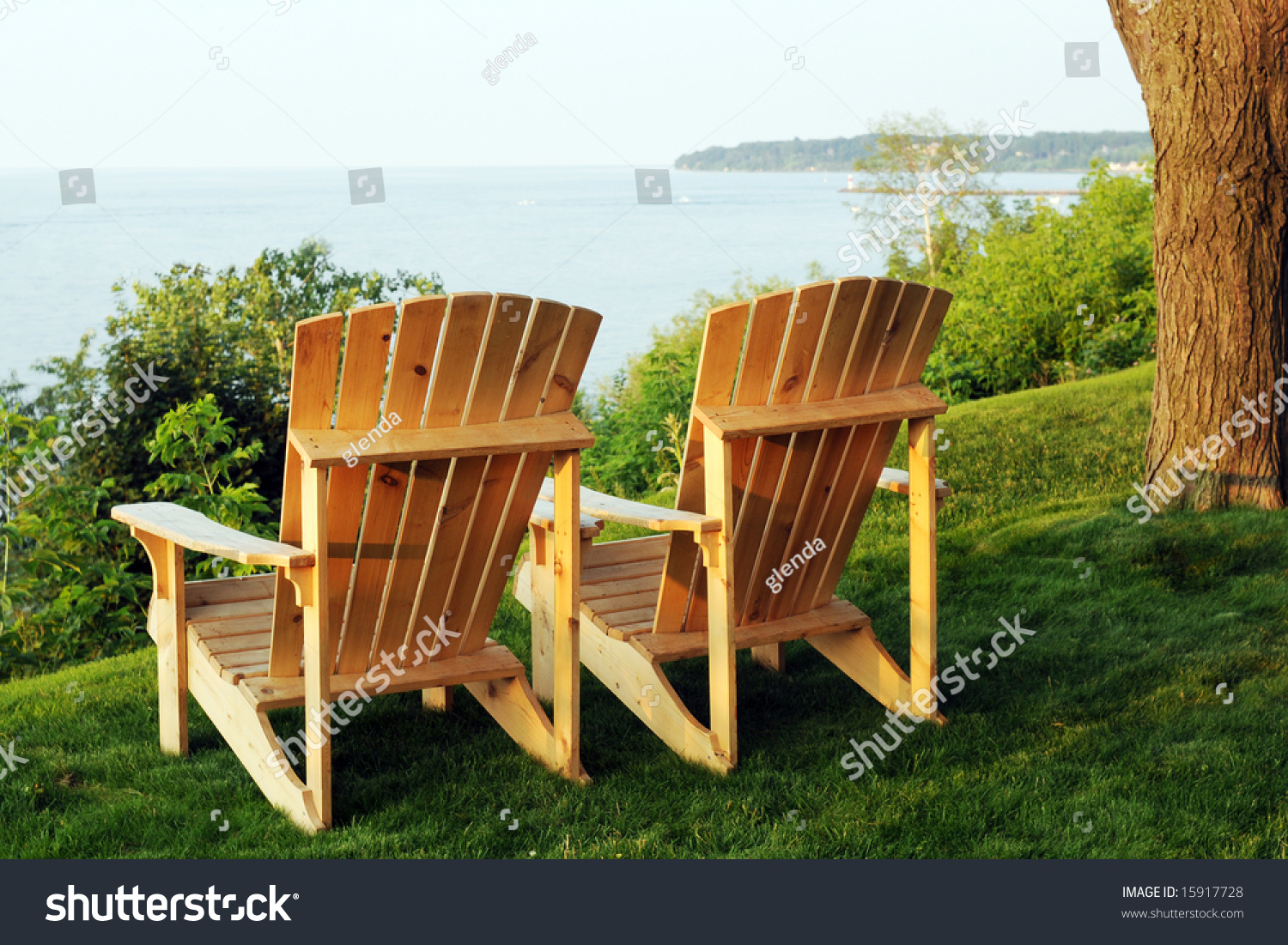 Two Adirondack Chairs On A Hillside Overlooking A Large Lake.