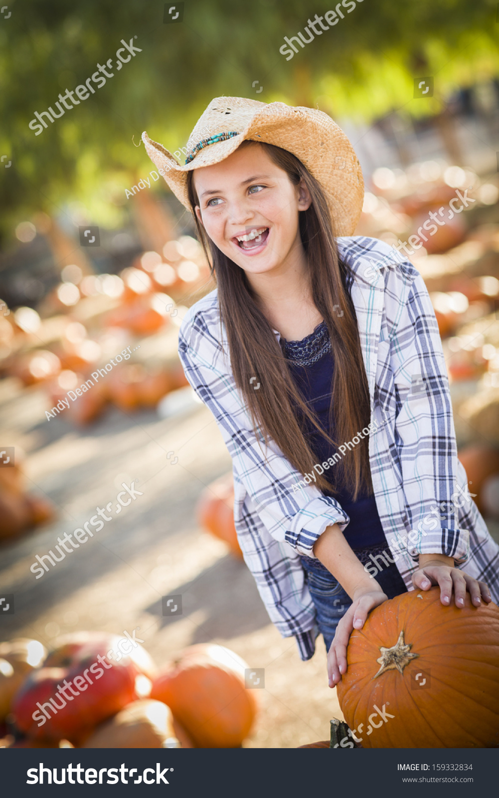 c794bd01f82 Preteen Girl Wearing Cowboy Hat Playing with a Wheelbarrow at the Pumpkin  Patch in a Rustic