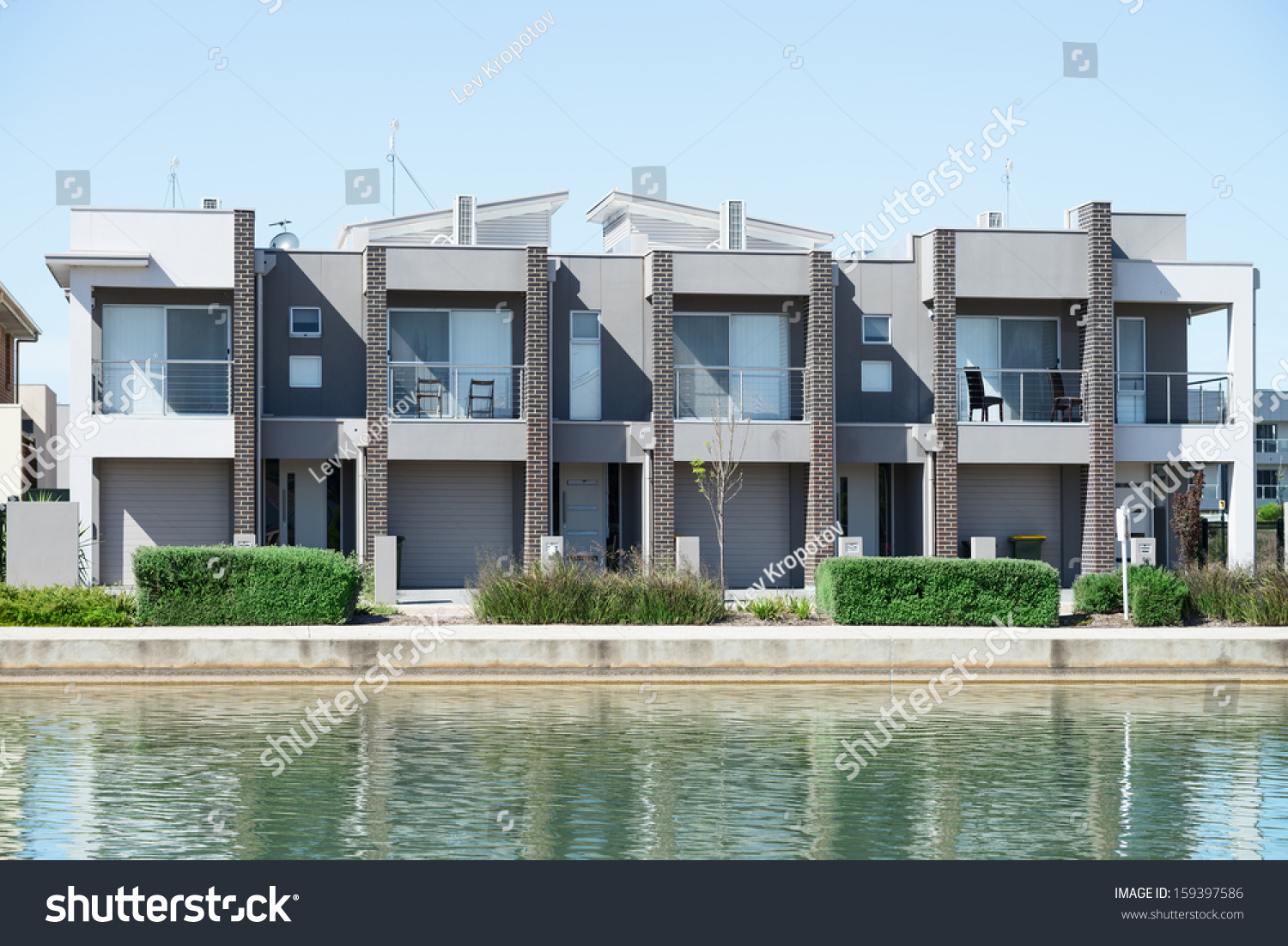 Modern Suburban House - Typical facade of a modern town suburban house near the pond at noon