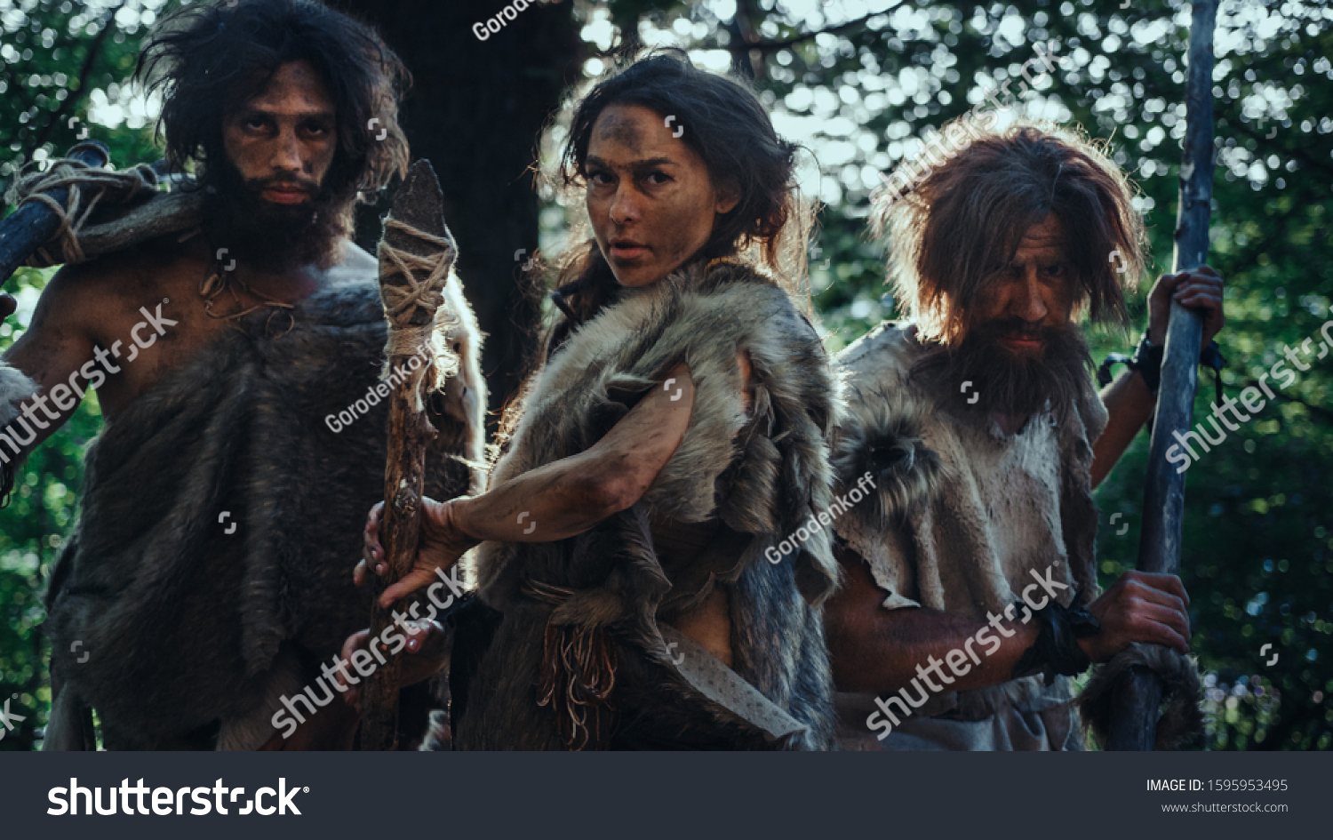 Female Leader and Two Primeval Cavemen Warriors Threat Enemy with Stone Tipped Spear, Scream, Defending Their Cave and Territory in the Prehistoric Times. Neanderthals / Homo Sapiens Tribe #1595953495