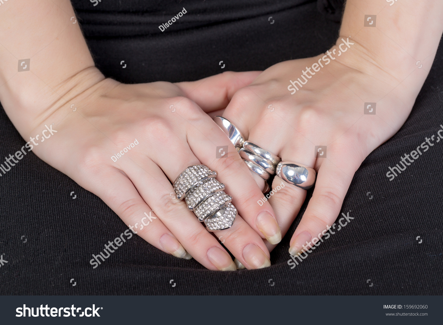 Closeup of the hands of a woman wearing multiple rings on her ...