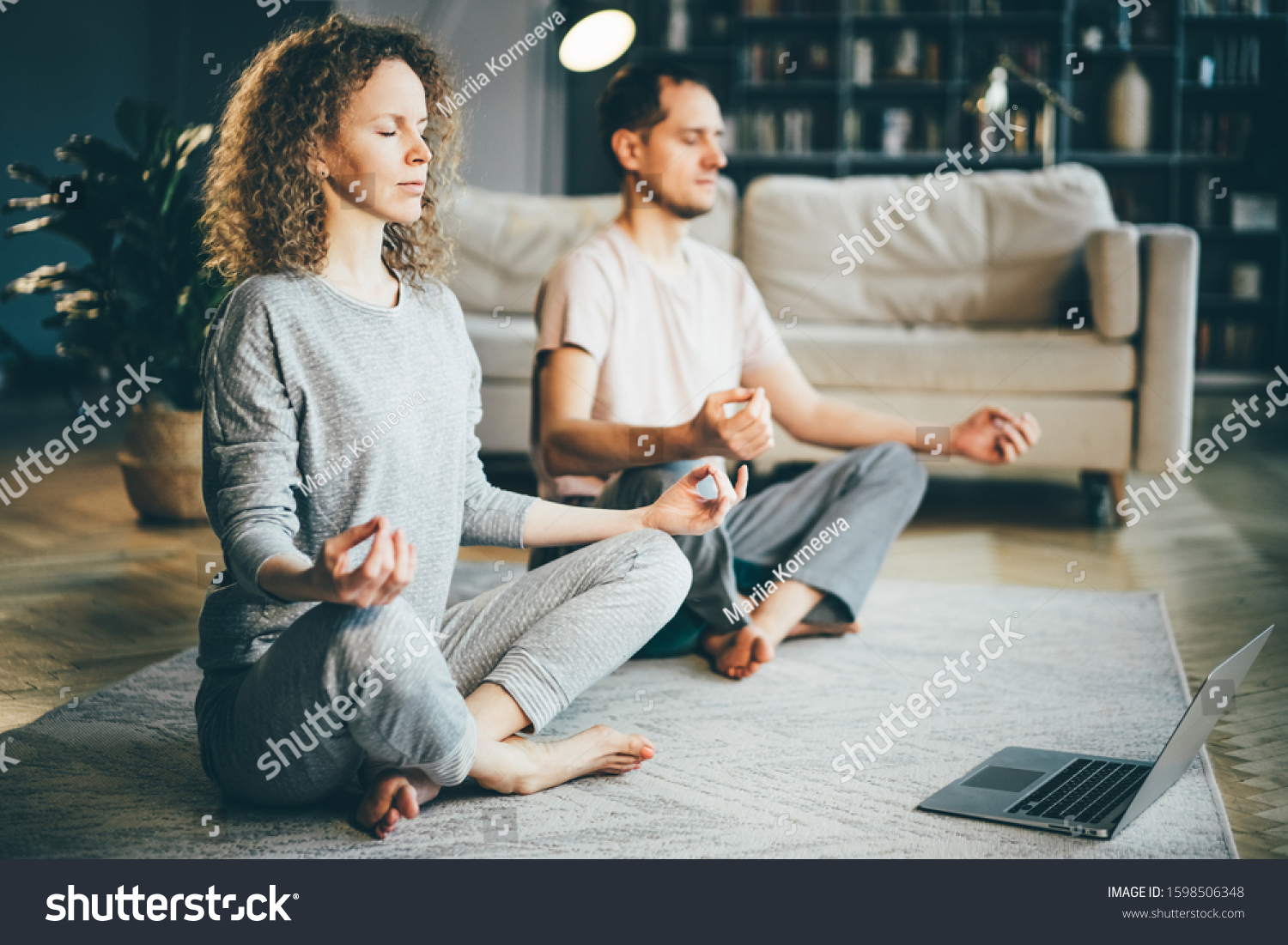 Calm couple in pajamas meditating, listening spiritual practices lessons on laptop, sitting on lotus pose at home. Yoga concept. #1598506348