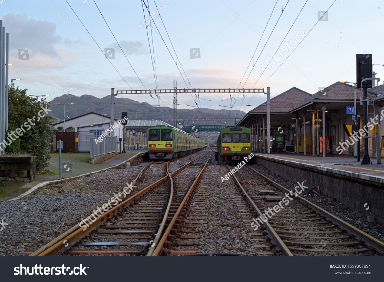 BRAY, CO. WICKLOW, IRELAND - DECEMBER 26, 2019: A front view of DART (Dublin Area Rapid Transit) trains at railway station in Bray, Ireland. Famous Bray Head mountain in the background.