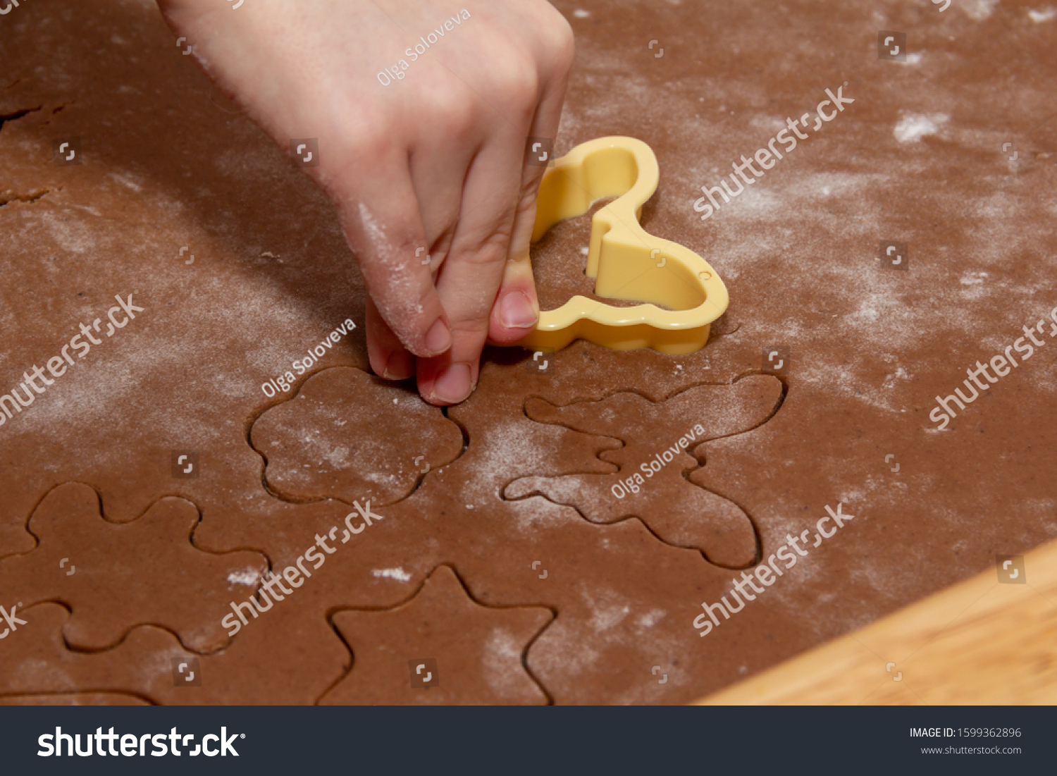 Cutting figures from the dough using special stencils for making ginger Christmas cookies. Children's hands close-up. Home, family prepare for the holidays concept. #1599362896