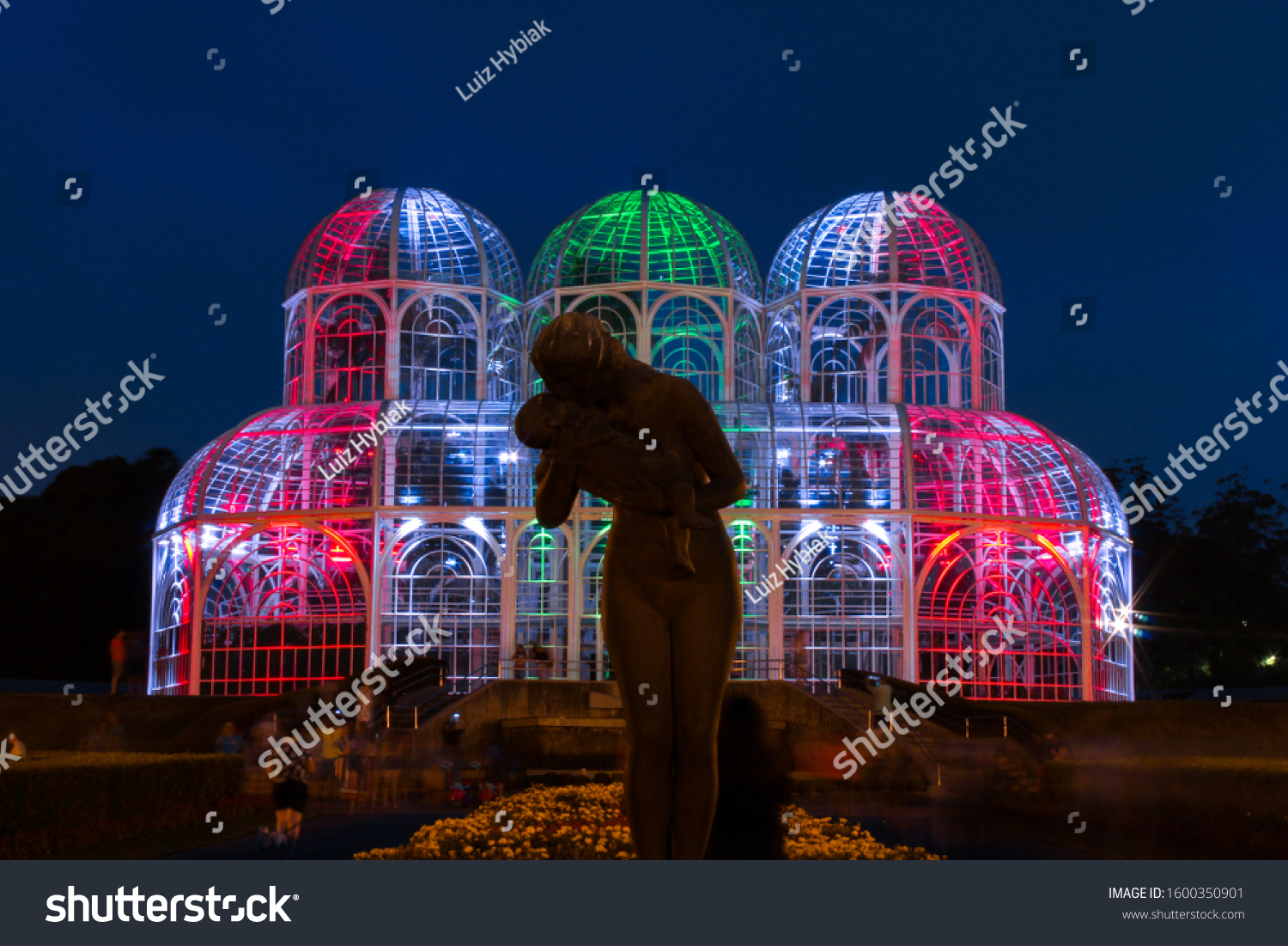 "Curitiba, Paraná, Brazil - December 28, 2019. Sculpture ""Amor Materno"" in Curitiba's Botanical Garden, main greenhouse in the background during the night. Green and red ilumination. Long exposure."