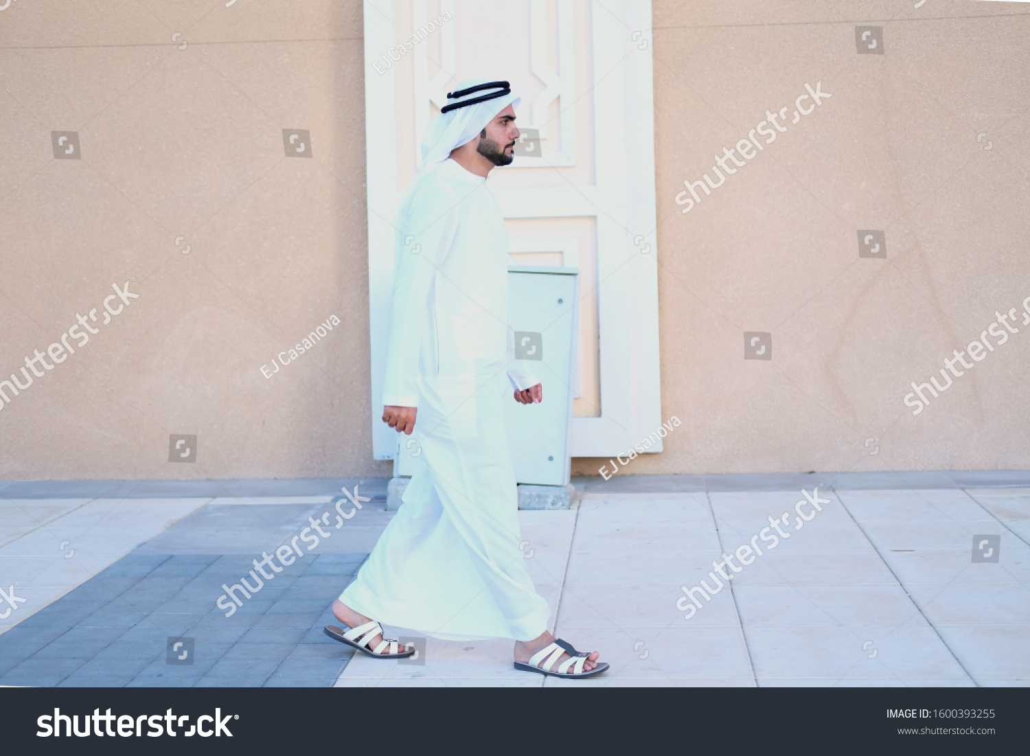 Full body portrait of Arab man walking on streets wearing Ghutra kandura. Emirati Arabic UAE National on dish dash. Side view of Arabian guy as he walks forward #1600393255