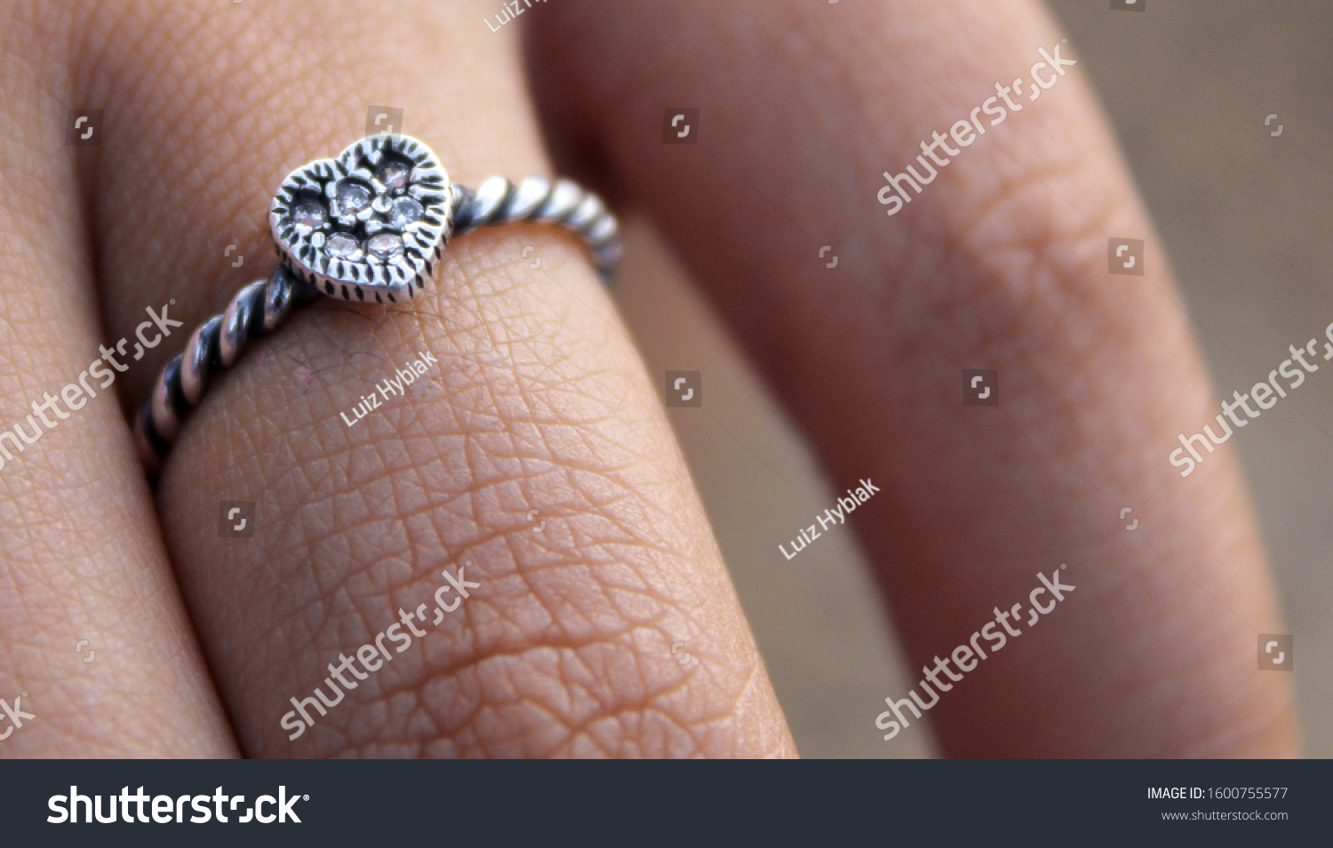 Woman wearing a heart shaped silver ring (finger close up). Twisted band ring. Dark skinned hand texture.