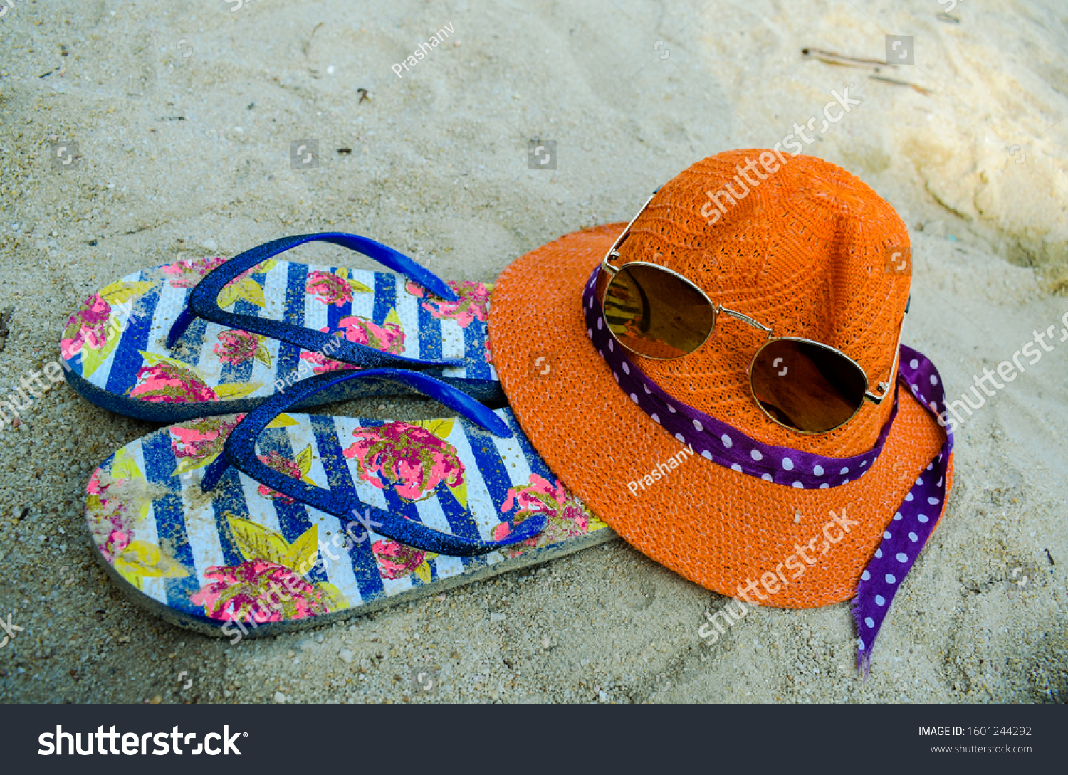 orange hat, flip flops and sunglasses on beach sand