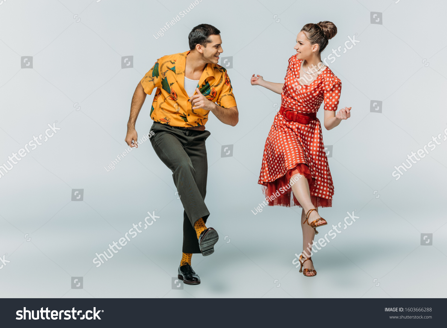 stylish dancers looking at each other while dancing boogie-woogie on grey background #1603666288