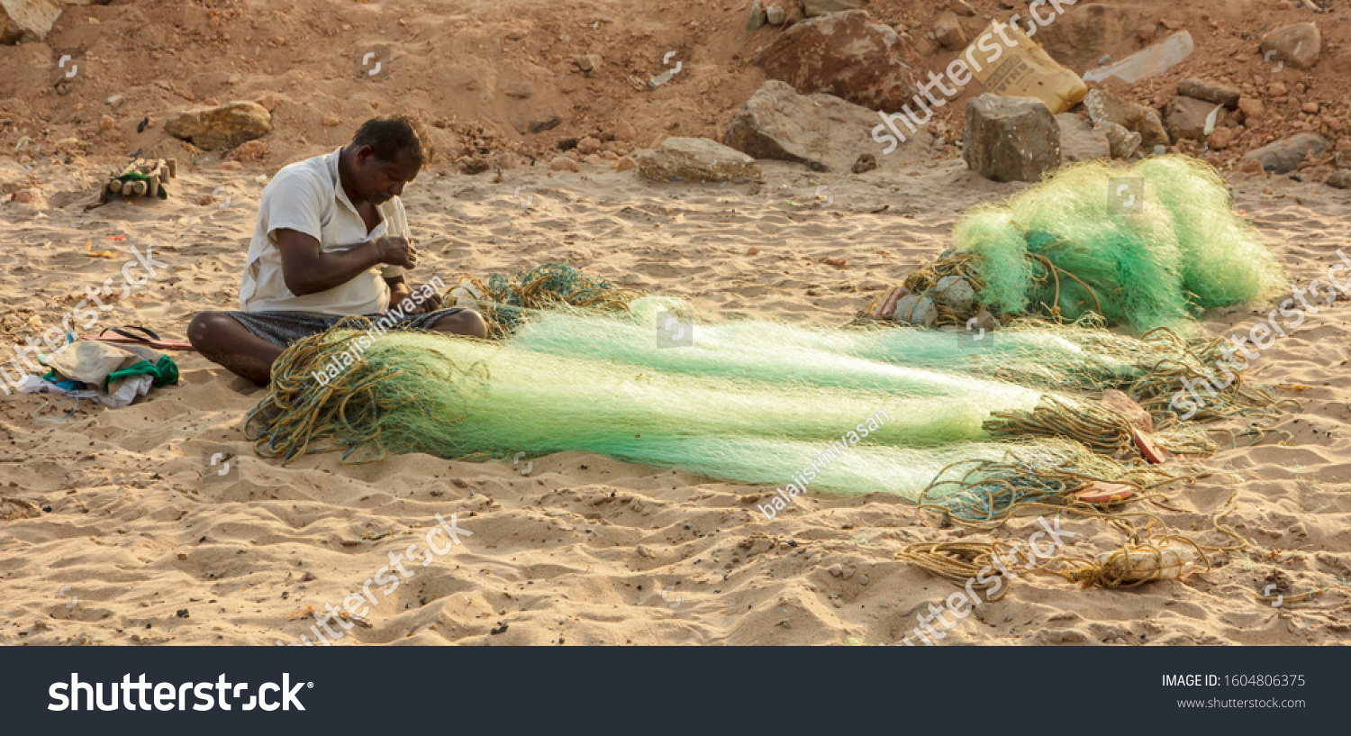 Visakhapatnam, Andhra Pradesh, India - February 2018: A fisherman sits on the beach and works at his green fishing nets in Rushikonda.