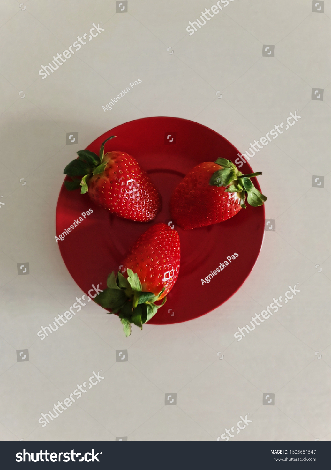 stock-photo-three-strawberries-on-red-pl