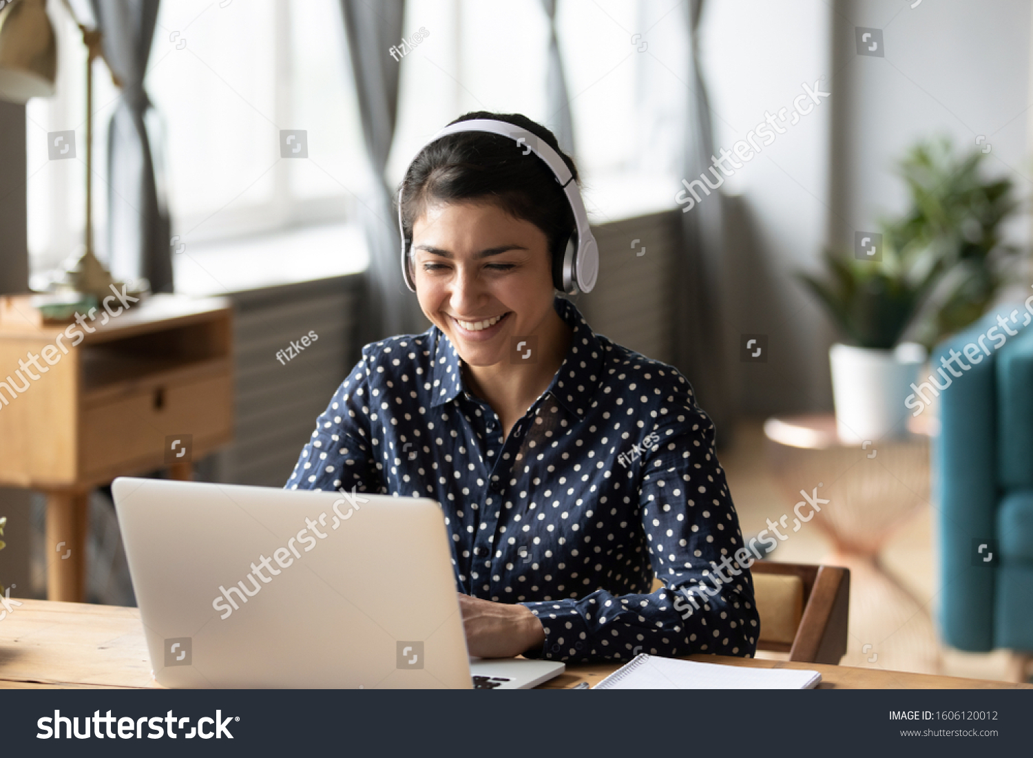 Happy indian young girl student wear headphone watch webinar listen online course communicate by conference video call e learn language in app laugh study with teacher lesson look at laptop at home #1606120012