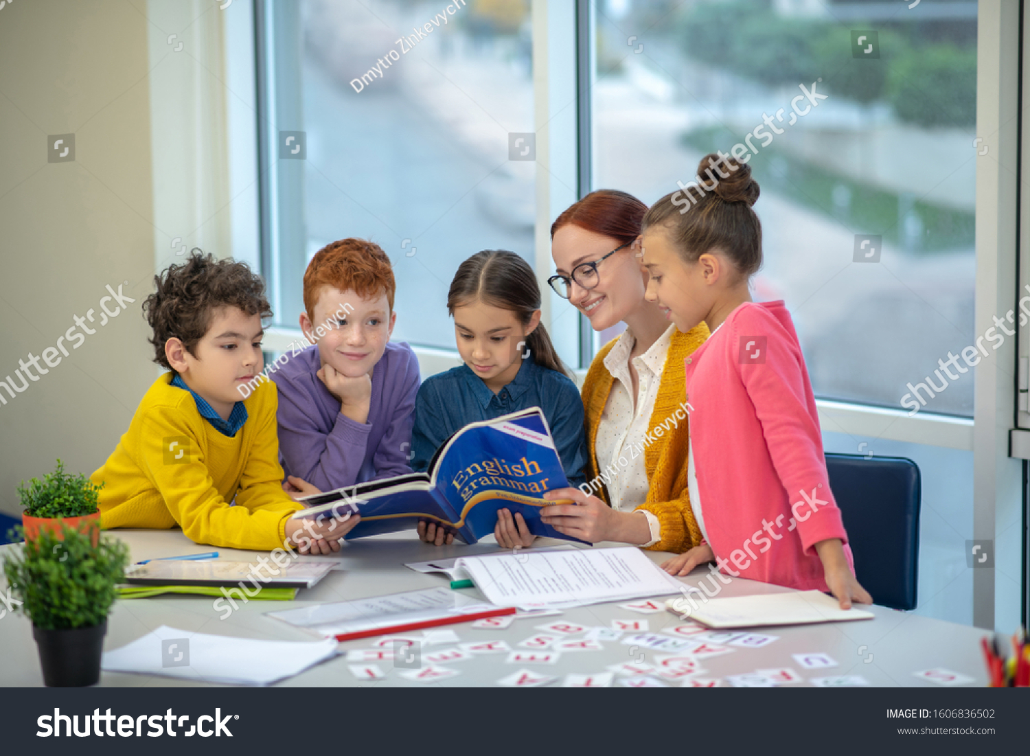 Learning English grammar. Children reading a book during their English class #1606836502