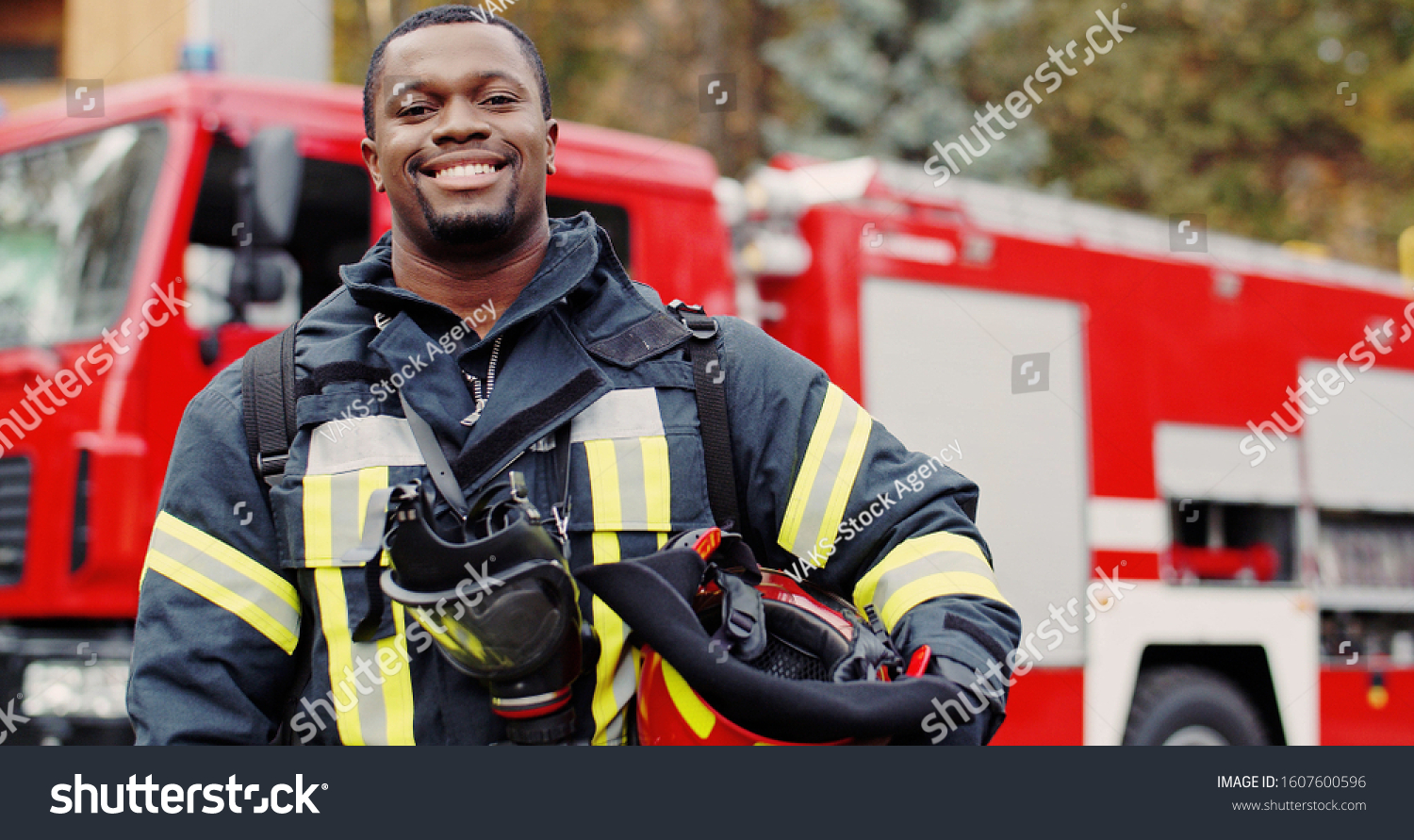 Firefighter portrait on duty. Photo of happy fireman with gas mask and helmet near fire engine #1607600596