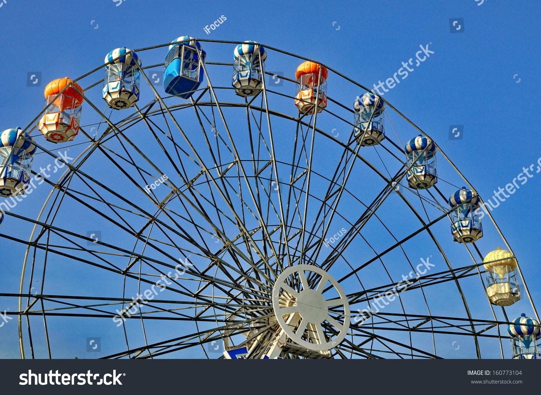 Ferris wheel in blue sky at amusement park