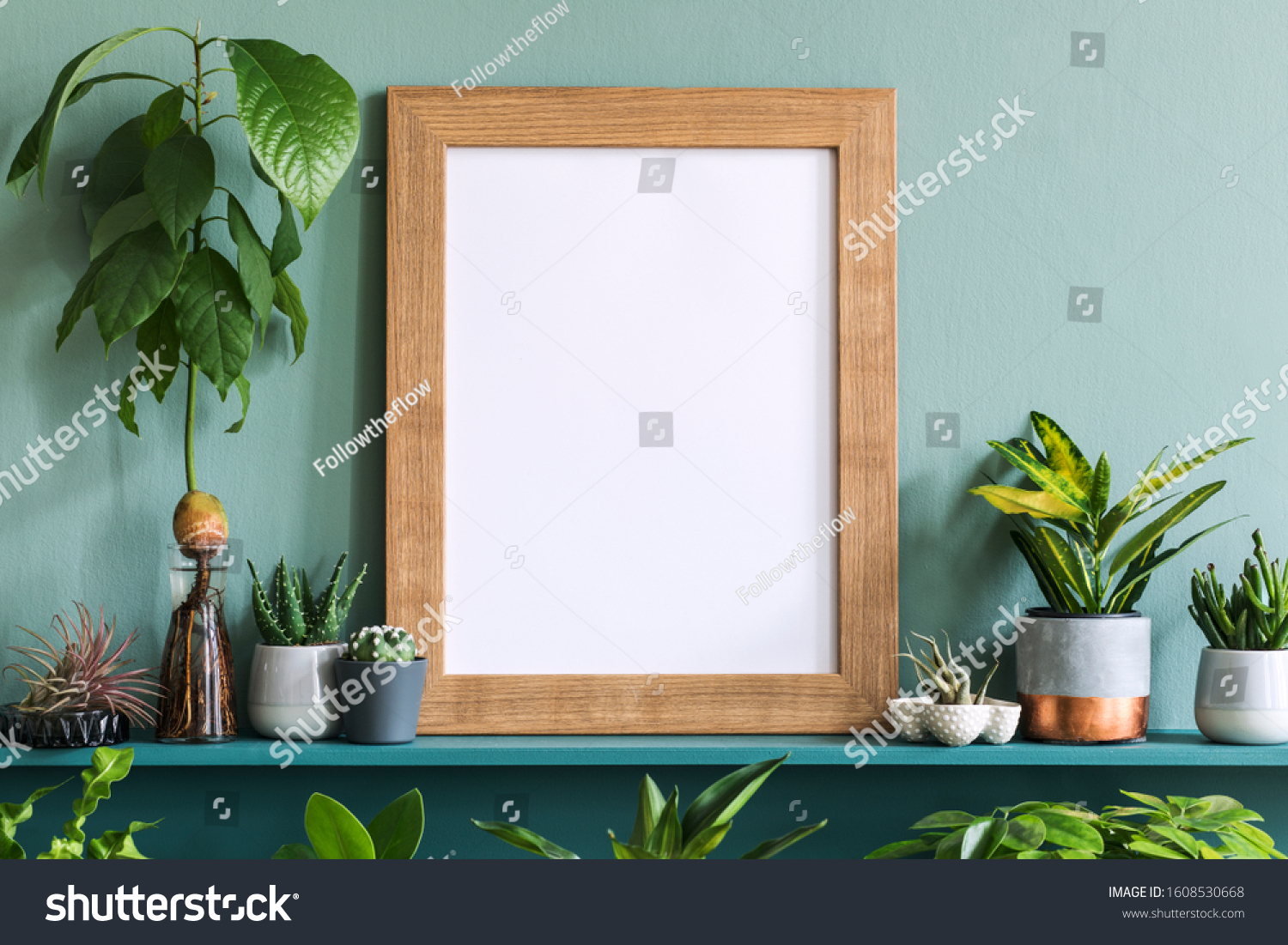 Interior design of living room with brown mock up photo frame on the green shelf with beautiful plants in different hipster and design pots. Elegant personal accessories. Home gardening. Template.