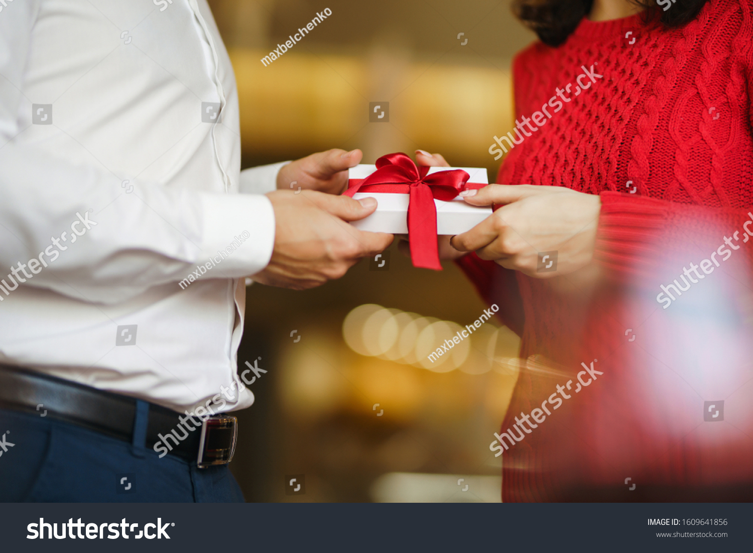 Man gives to his woman a gift box with red ribbon. Hands of man gives surprise gift box for girl. Lovers give each other gifts. Young loving couple celebrating Valentine's Day. Romantic day. #1609641856