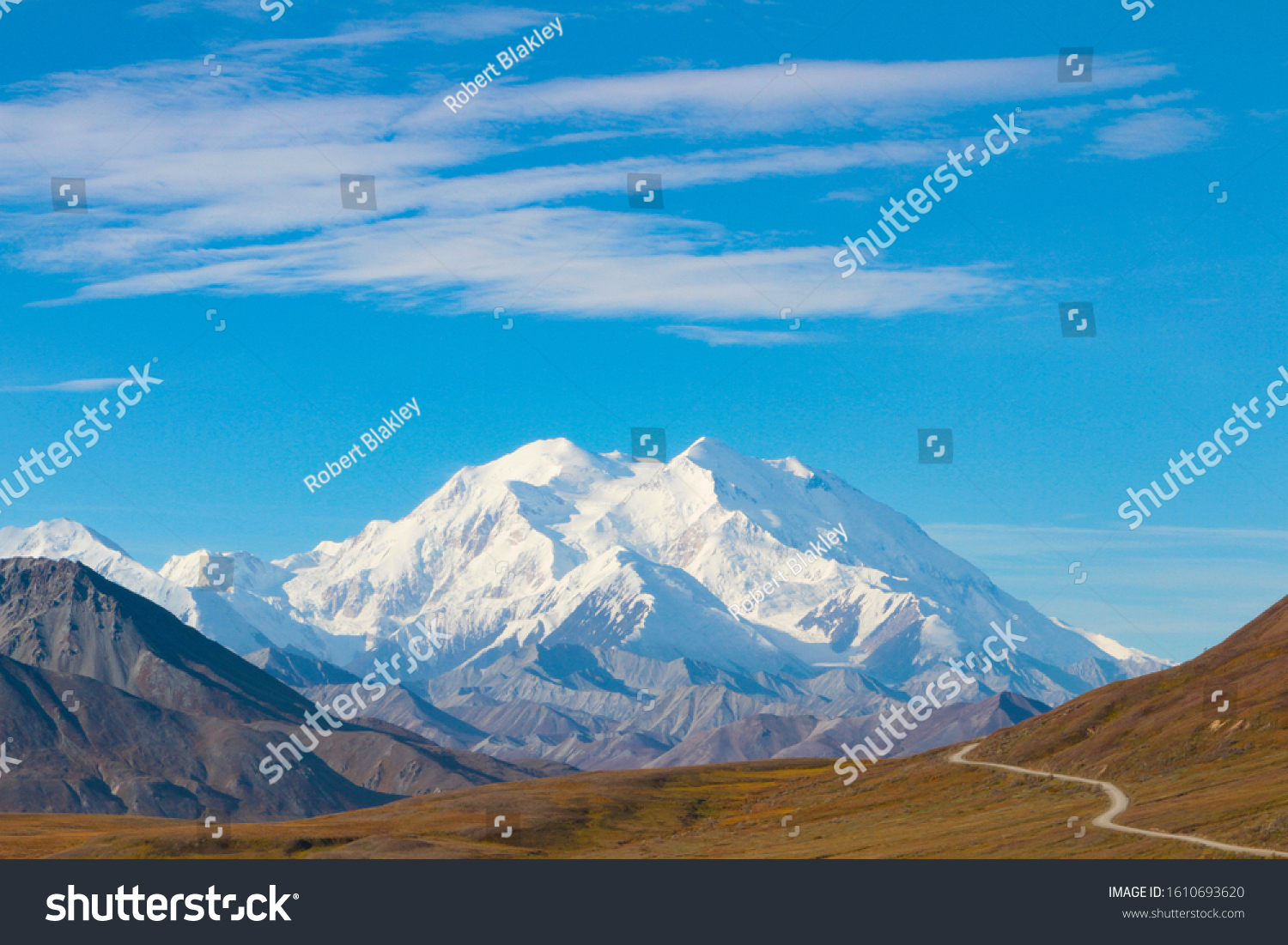 Winding Road Leading to Denali Mountain in Alaska With Blue Sky and Cloud Floating Above the Mountain