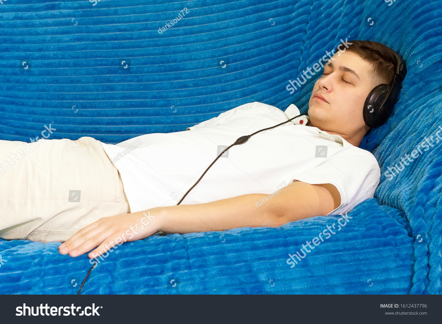 a young man in a white t-shirt at home listening to relaxing music. relaxation relaxation, calmness #1612437796