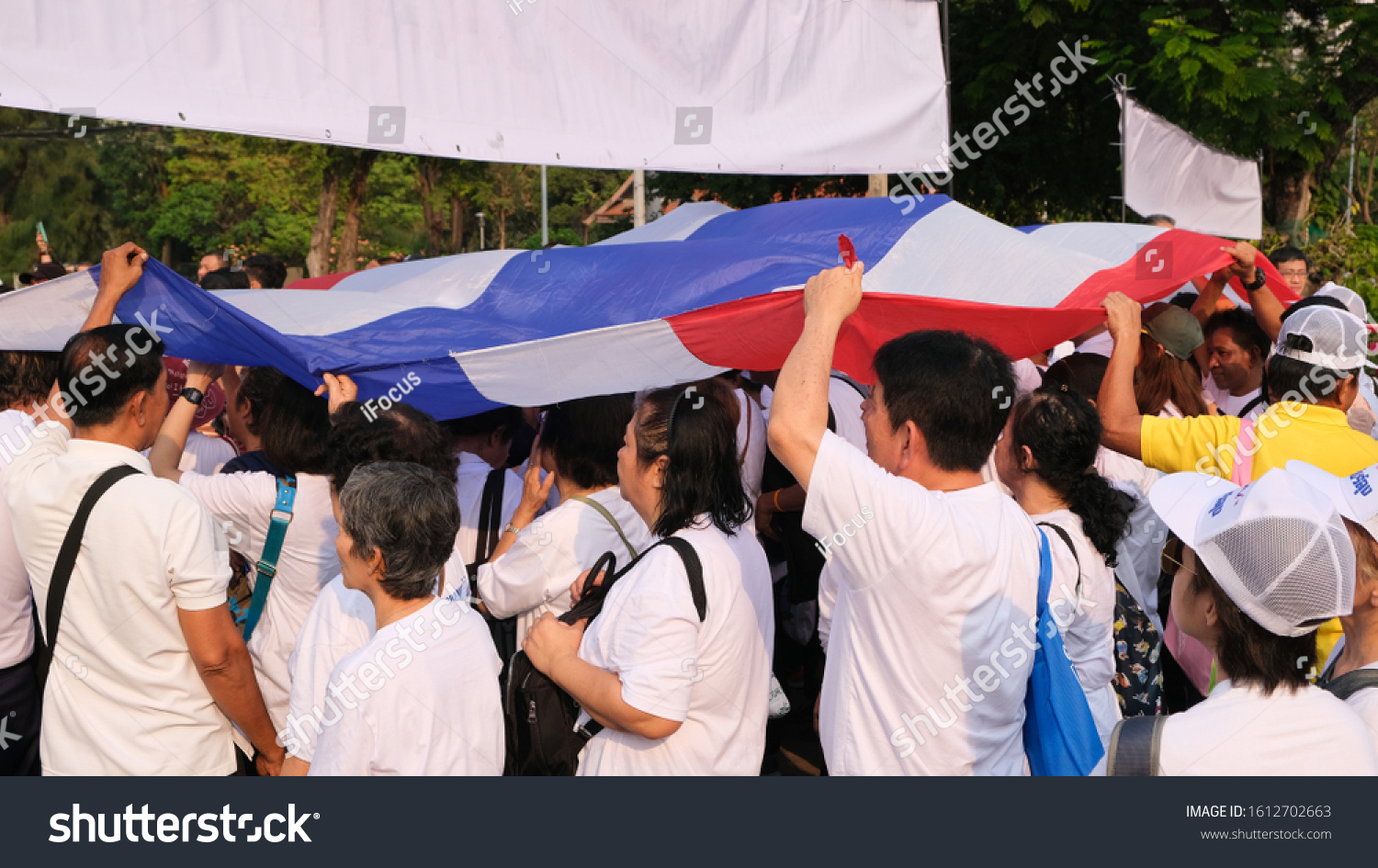 BANGKOK, THAILAND - JANUARY 12, 2020: People walk under a large Thai flag at an event showing support to Prime Minister Prayut on January 12, 2020 in  Thai capital Bangkok