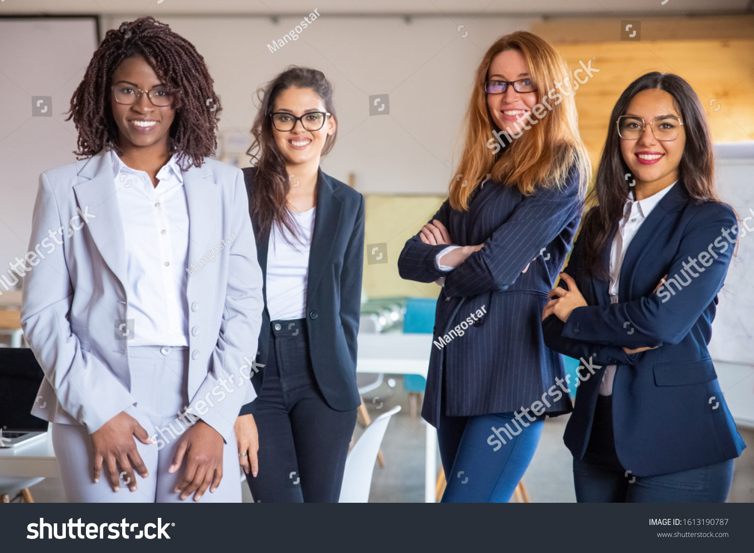 Group of confident young women looking at camera. Beautiful smiling businesswomen posing in modern office. Female confidence concept #1613190787