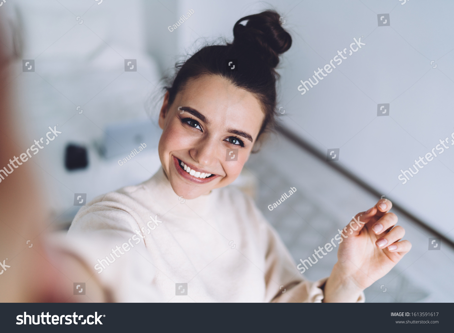 Pretty young female with big smile standing at bedroom after work with laptop and having fun taking light cheerful selfie on blurred background #1613591617