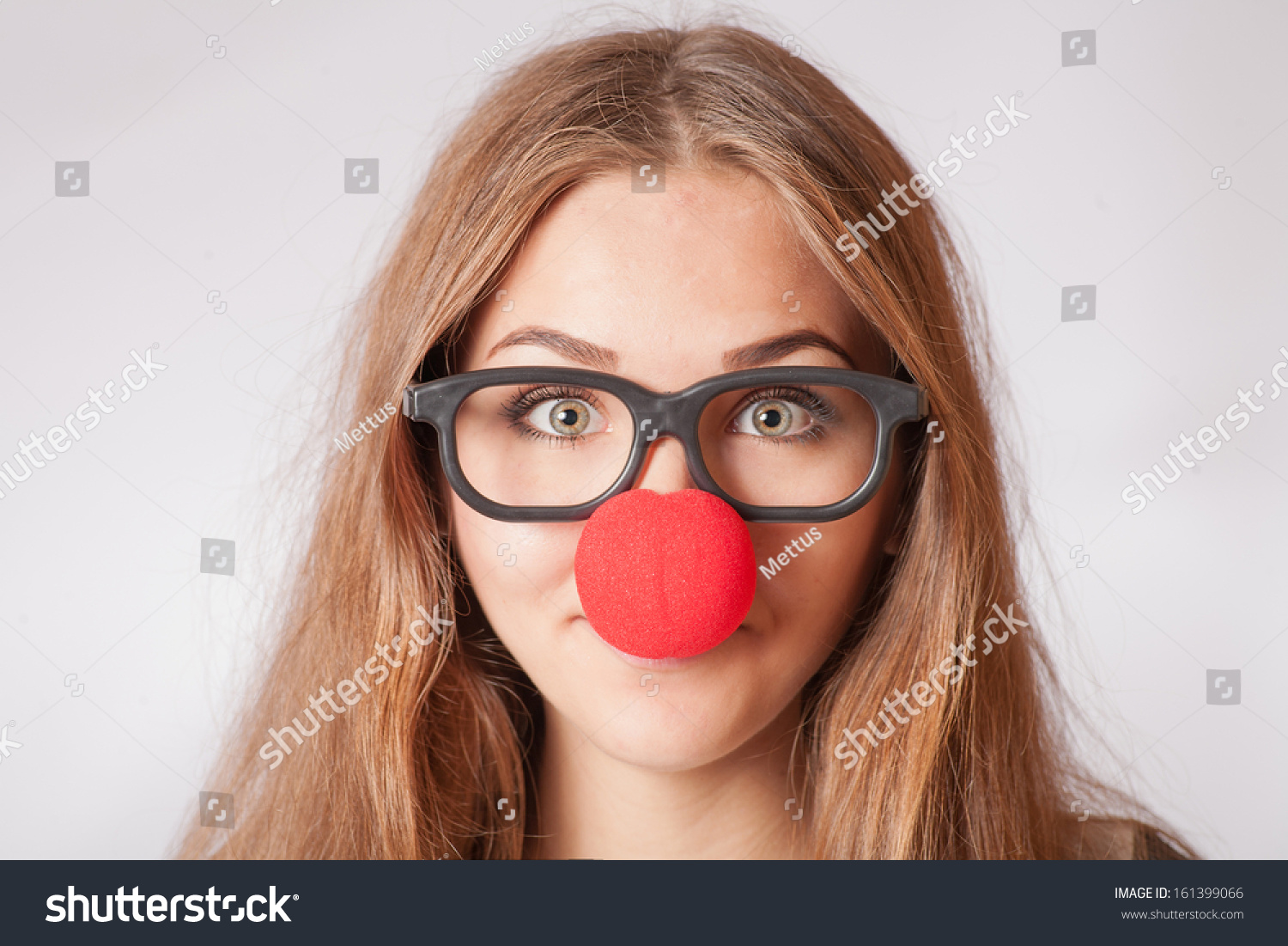 Close-up portrait of a happy 20s girl with red clown nose. Funny portrait of young woman in party glasses