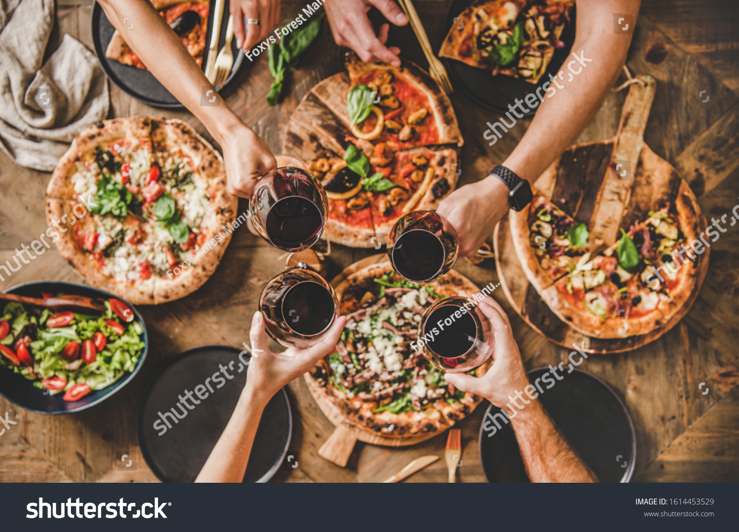 Family or friends having pizza party dinner. Flat-lay of people clinking glasses with red wine over rustic wooden table with various kinds of Italian pizza, top view. Fast food lunch, celebration #1614453529