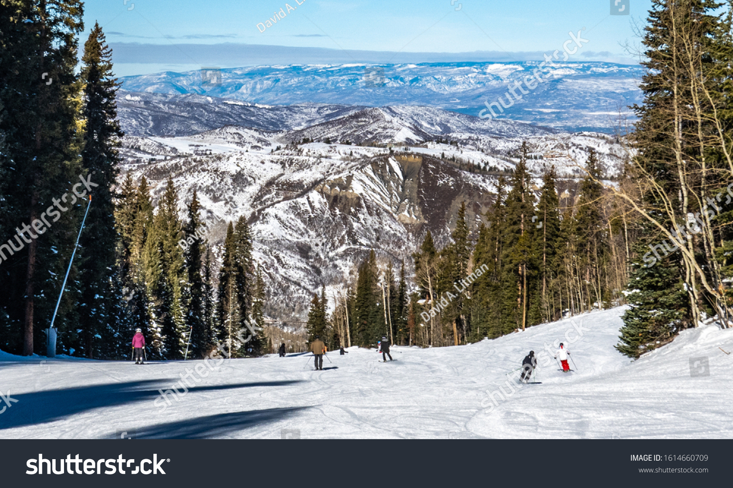 Skiers and snowboarders descend the slopes of the Aspen Snomass ski resort, in the Rocky Mountains of Colorado.