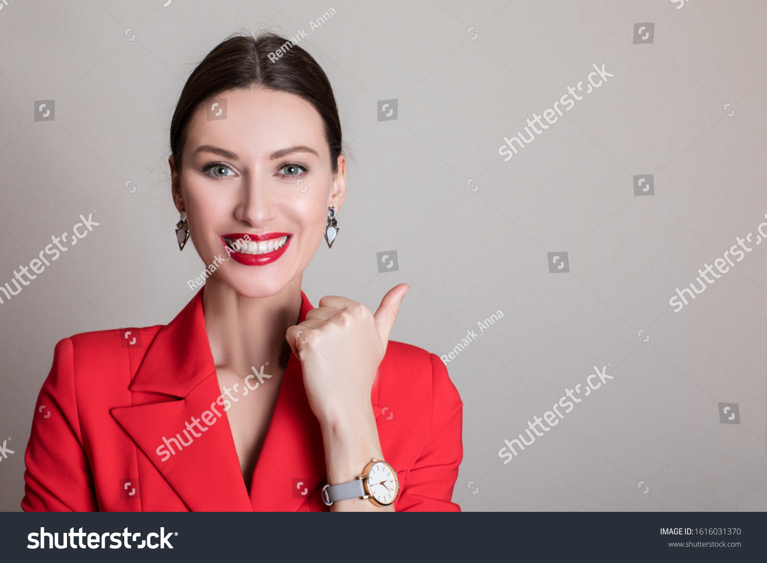 Girl bank worker in a red blazer smiles a snow-white smile showing class gesture. Isolated portrait of smiling business woman #1616031370