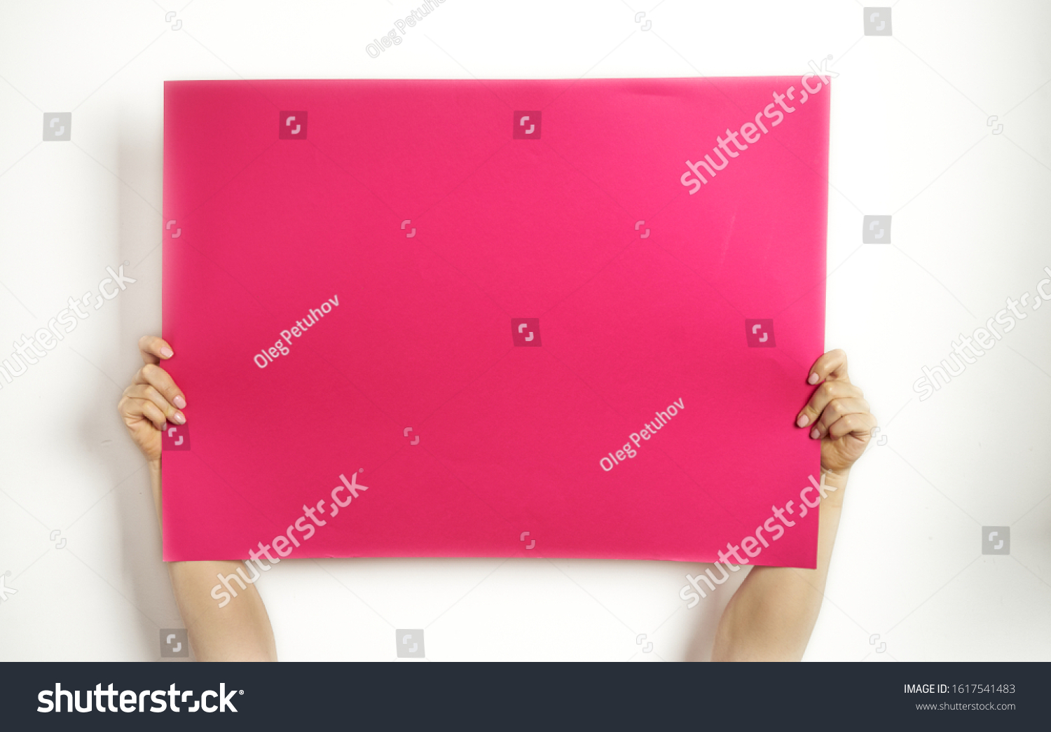 A large sheet of red paper in hands on a white background. Copy space. Woman hold blank card.   #1617541483