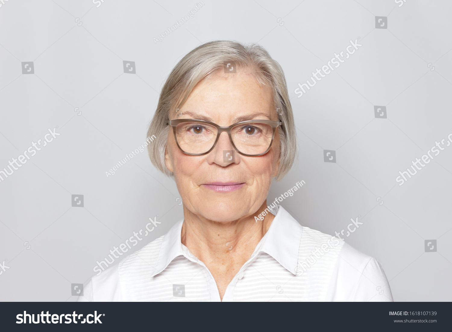 Portrait picture of a senior woman wearing glasses on neutral gray background. #1618107139