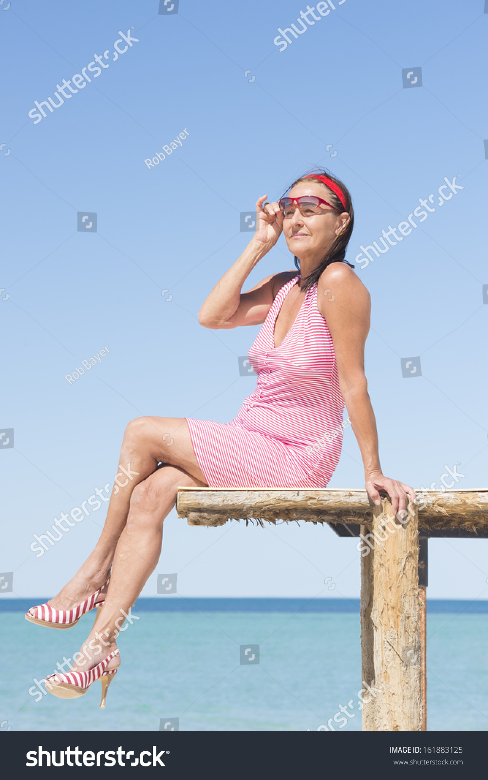 beautiful mature woman sitting sexy pose stock photo (royalty free