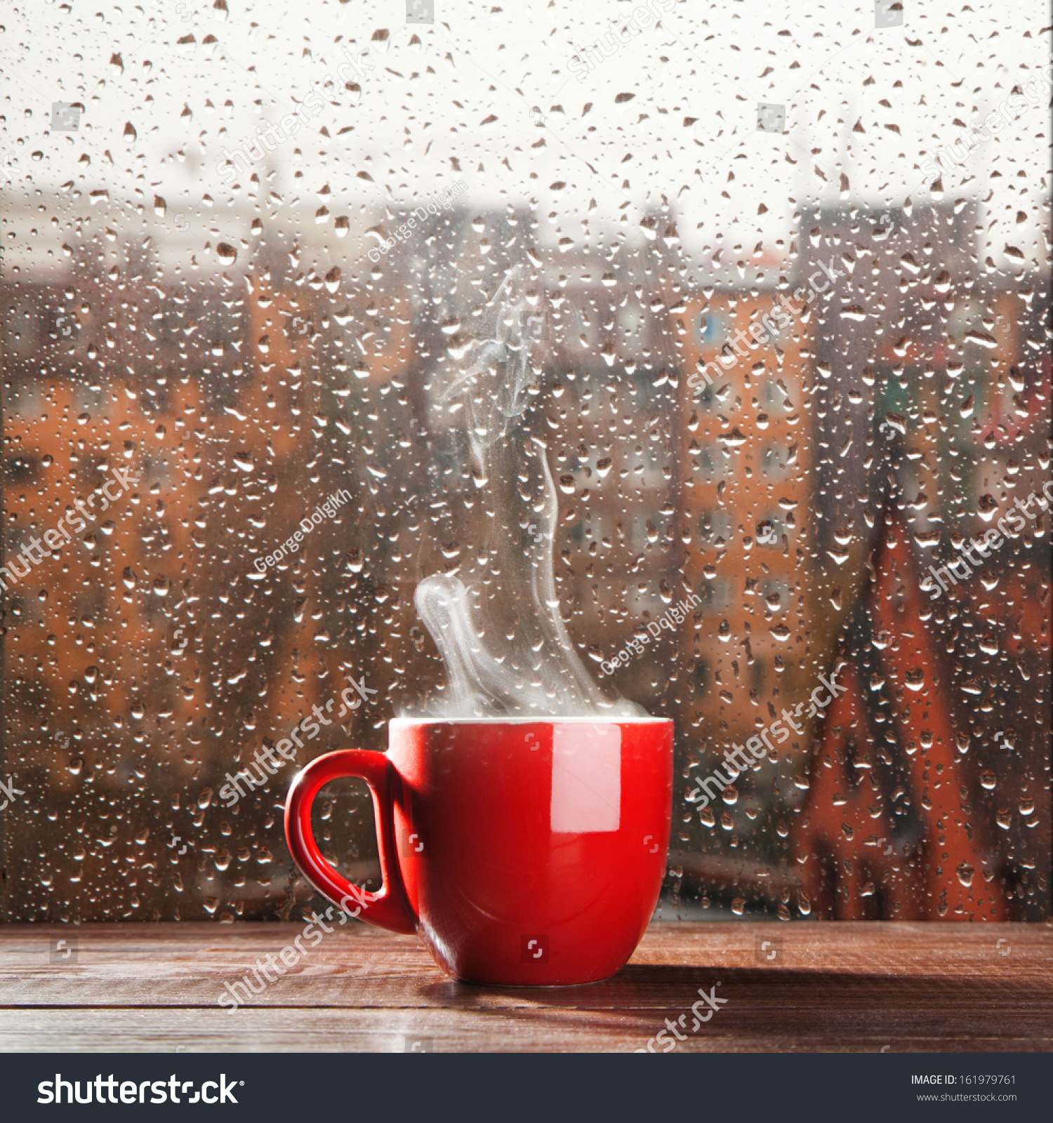 steaming coffee cup on rainy day stock photo 161979761