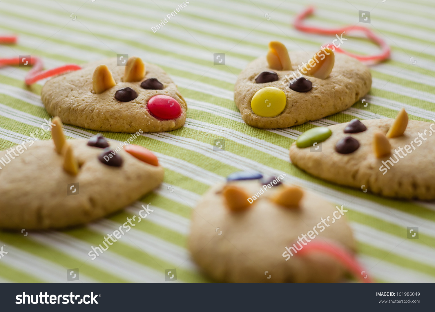 Cookies With Mouse Shaped And Red Licorice Tail Over Green Striped  Tablecloth